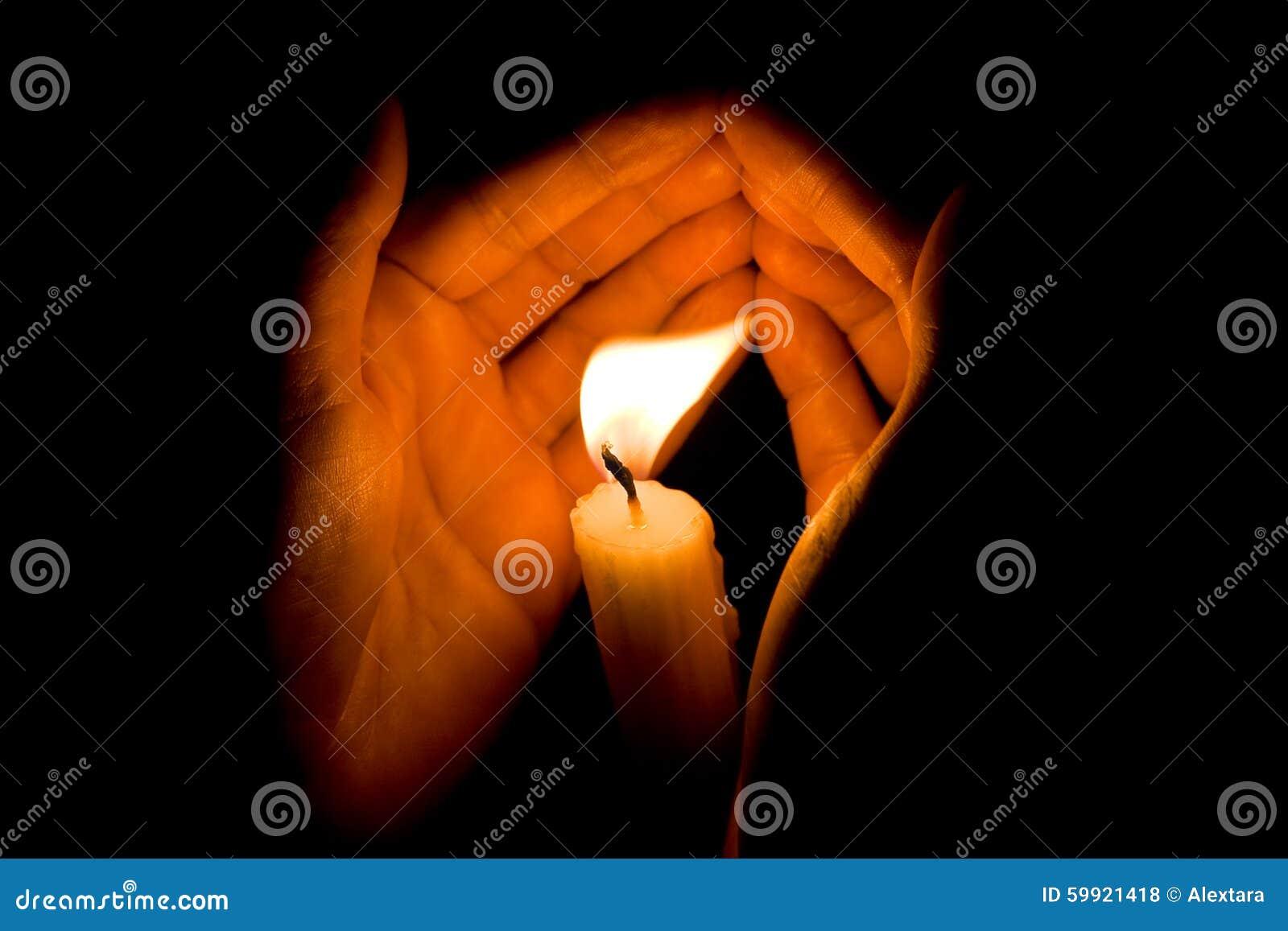 As mãos protegem a luz de vela brilhante na escuridão