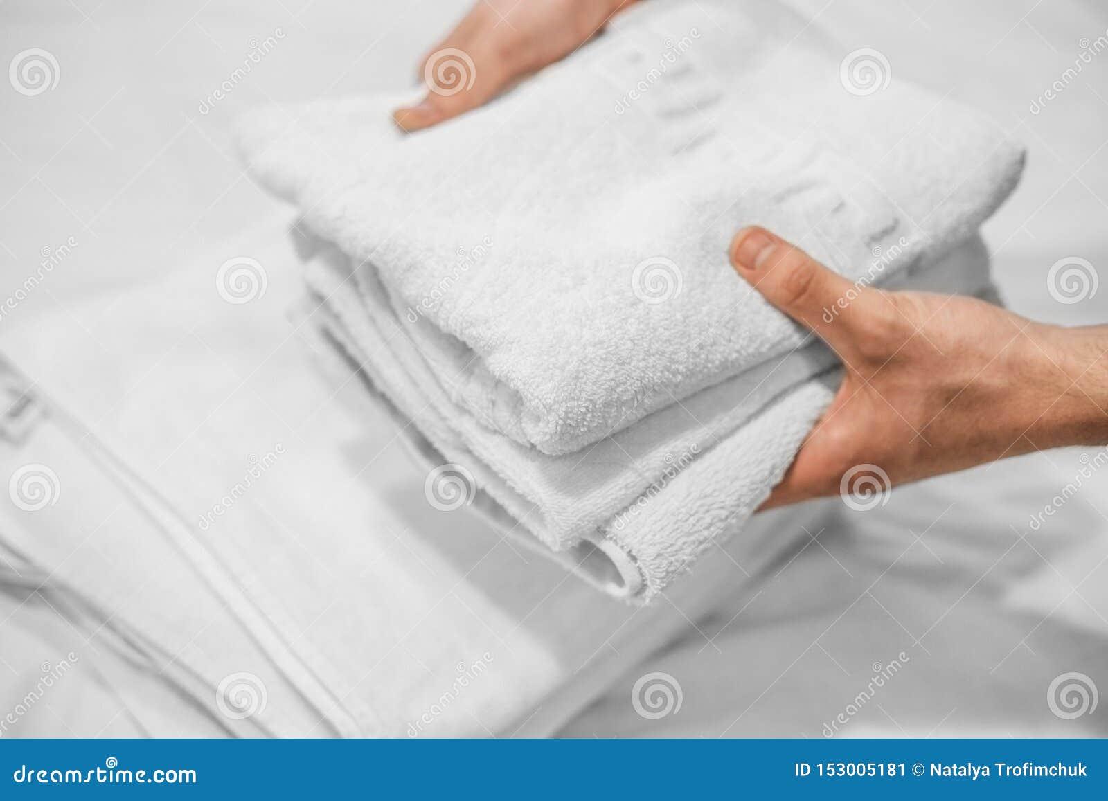 As mãos puseram as toalhas brancas sobre uma cama branca Neg?cio do hotel