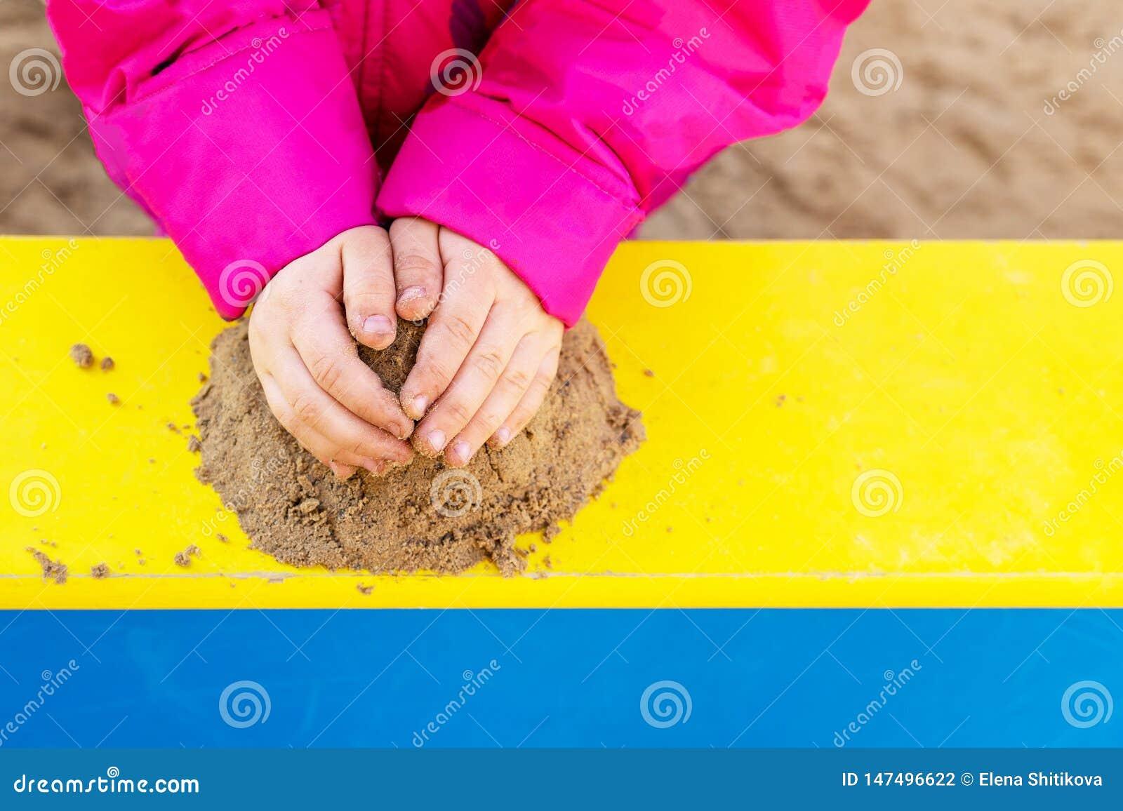 As m?os de uma crian?a que joga com areia