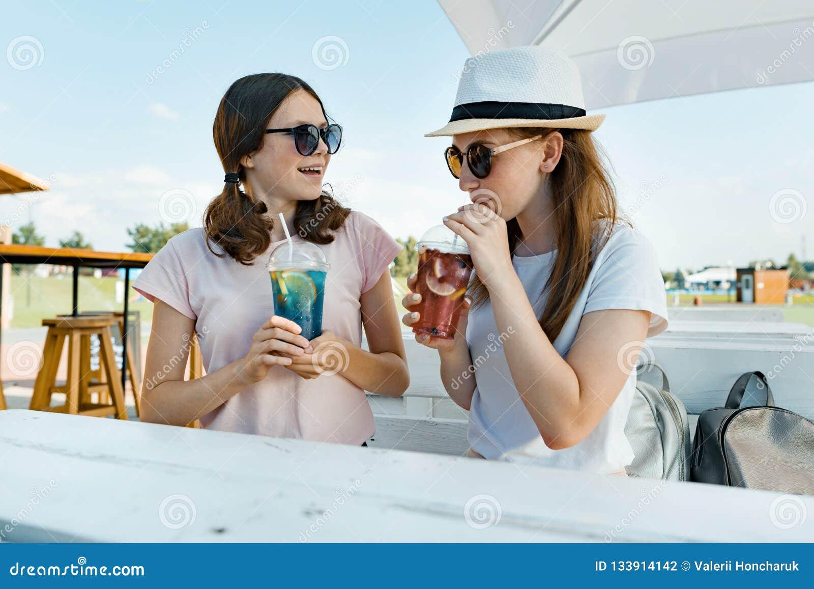 As meninas adolescentes de sorriso novas bebem bebidas de refrescamento frescas do verão em um dia ensolarado quente no café exte