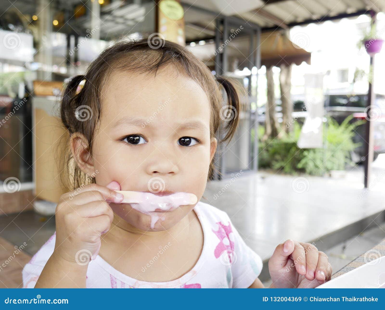 As meninas asiáticas pequenas do foco seletivo estão felizes comer um gelado delicioso, espaço da cópia