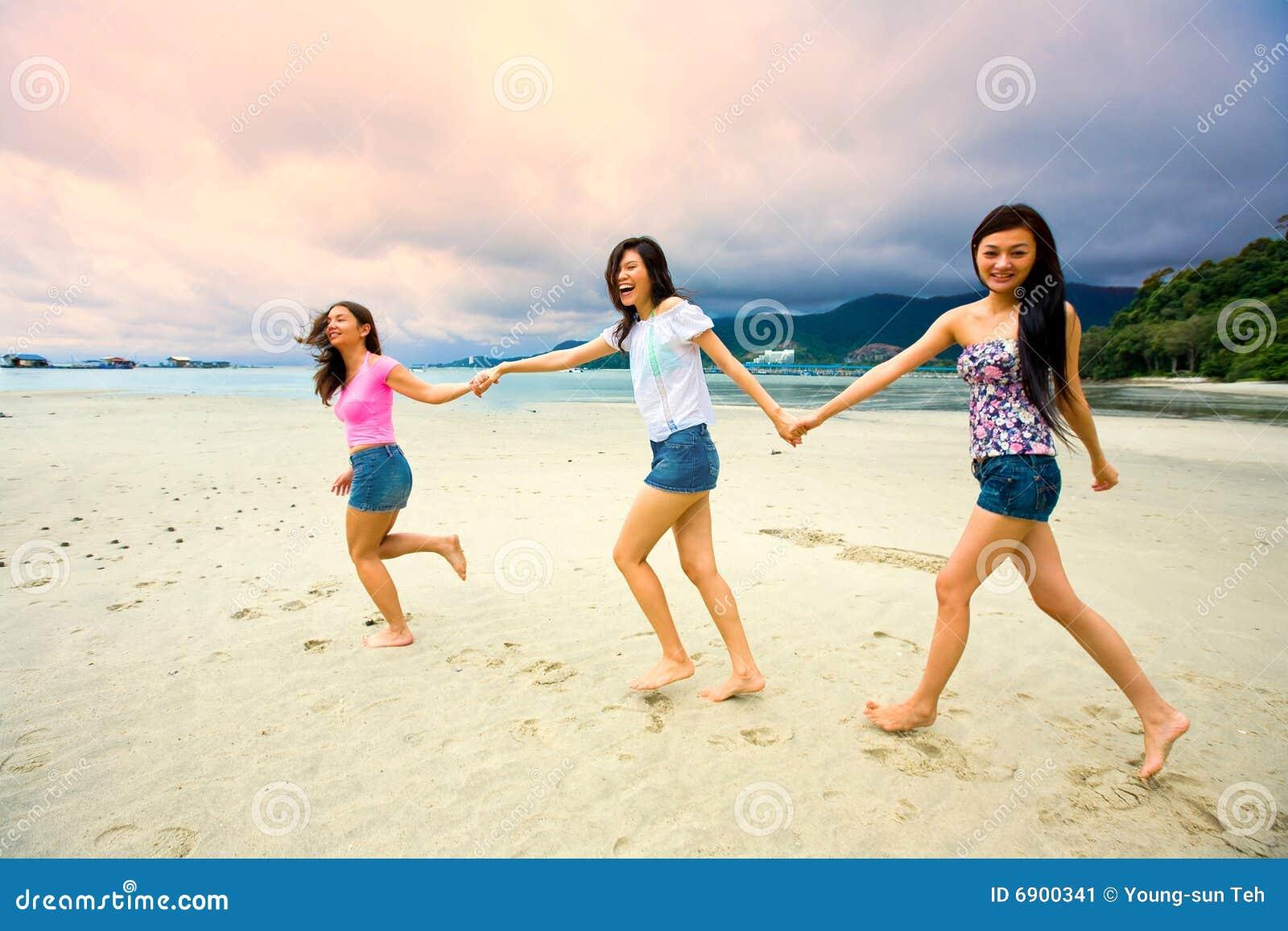 As meninas asiáticas têm o divertimento na praia
