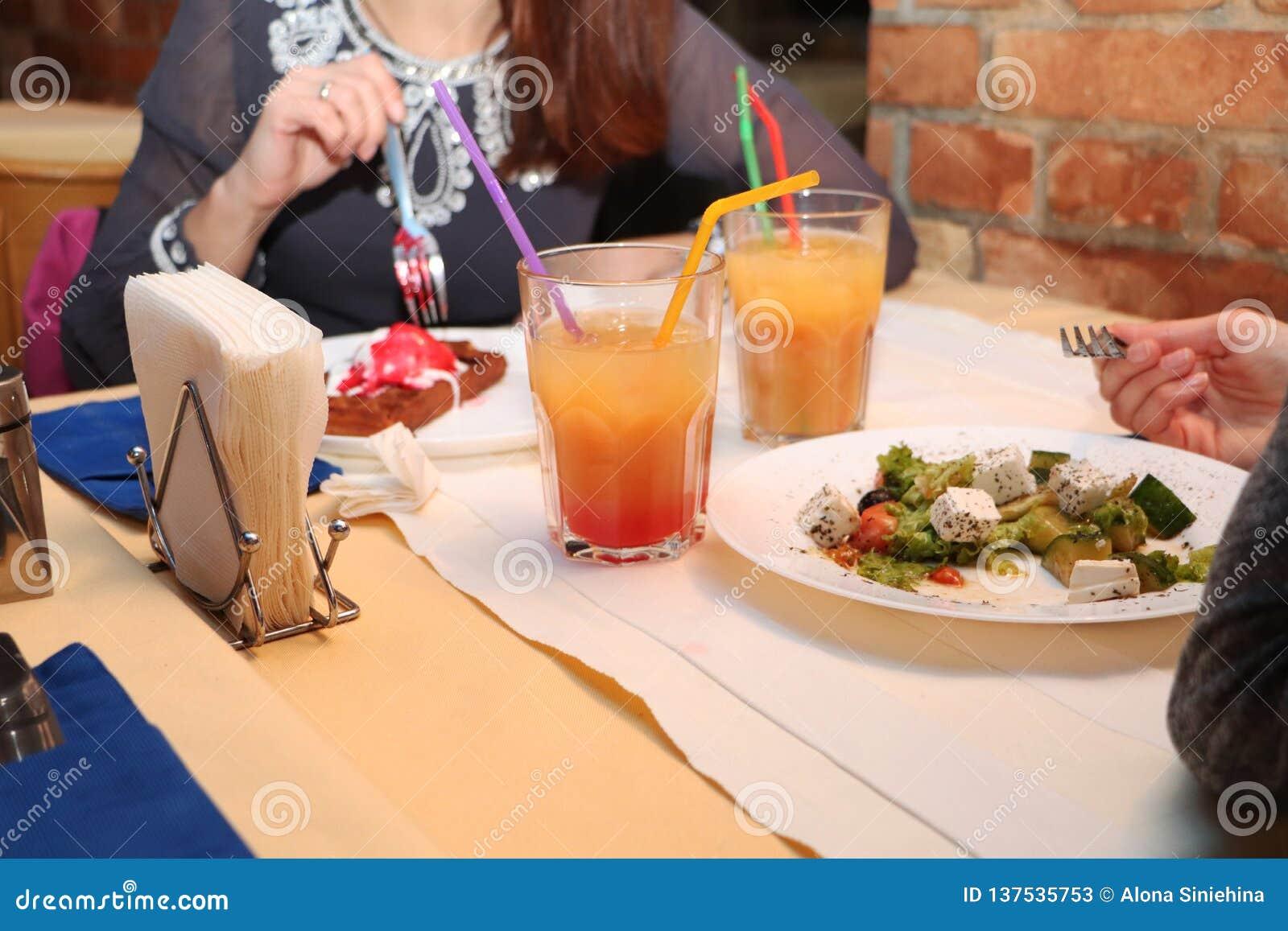 As meninas comem a salada grega em um restaurante e em cocktail da bebida