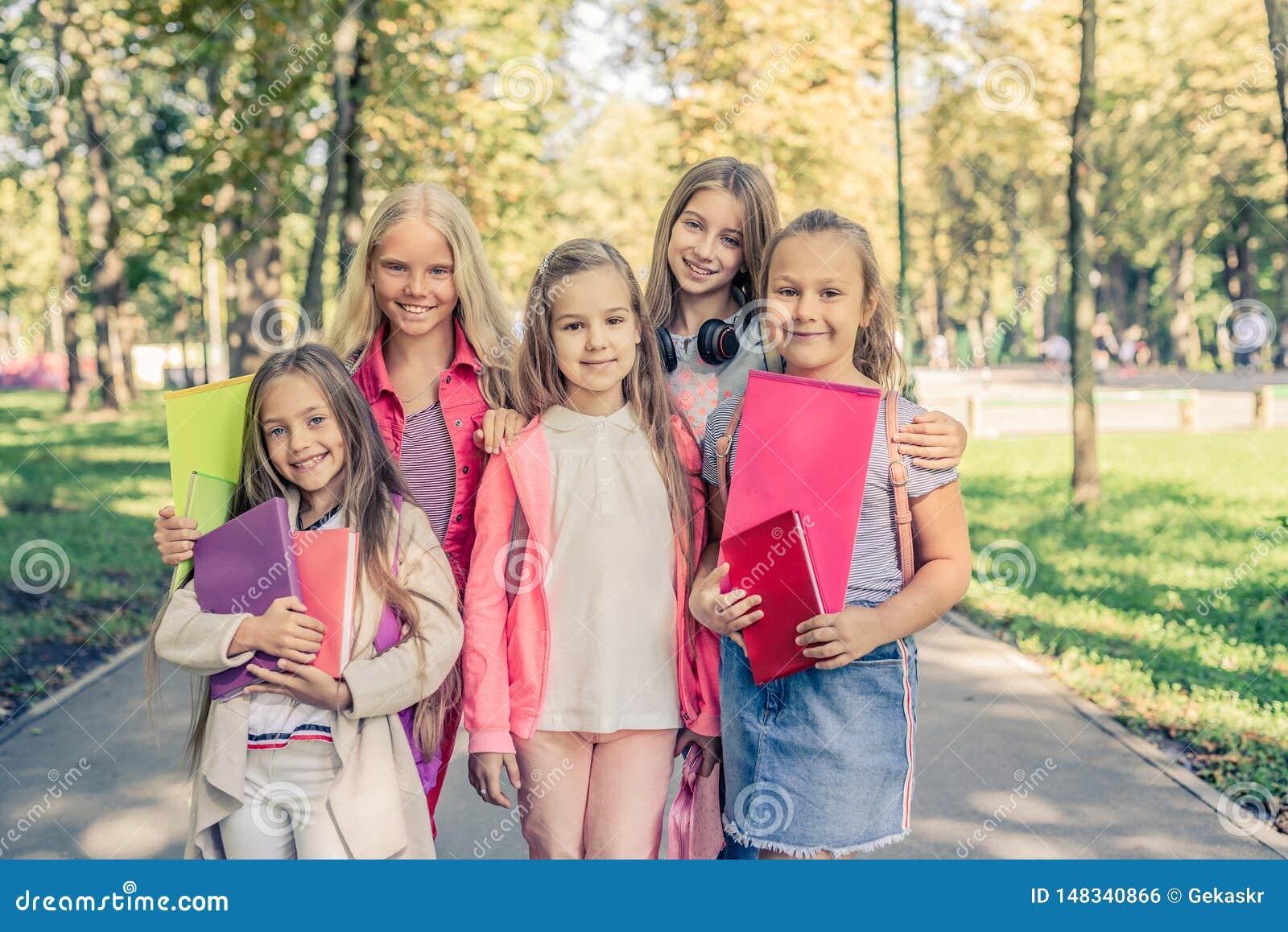 As meninas de sorriso bonitas est?o junto no parque da luz do sol
