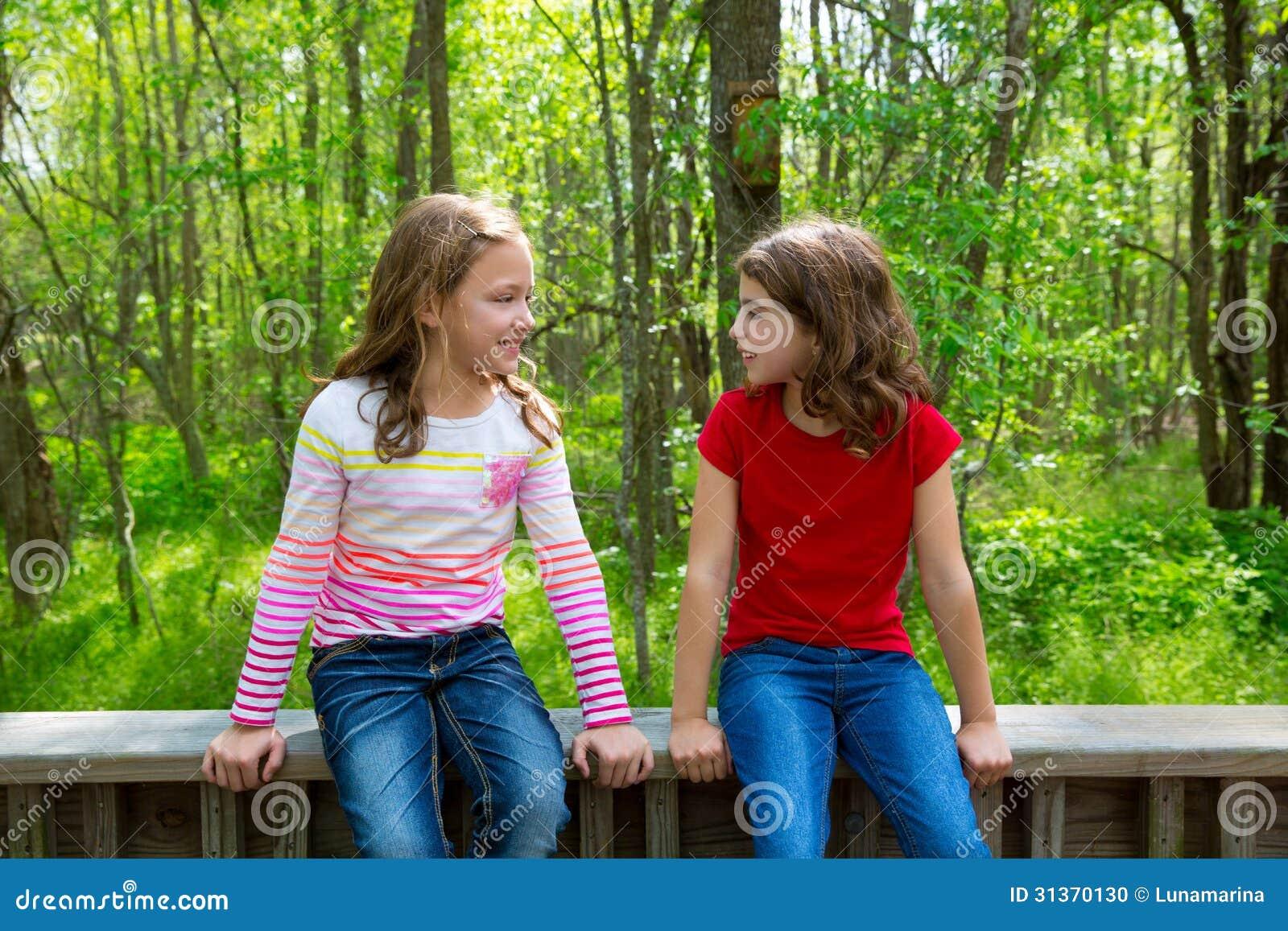 As meninas do amigo das crianças que falam na selva estacionam a floresta