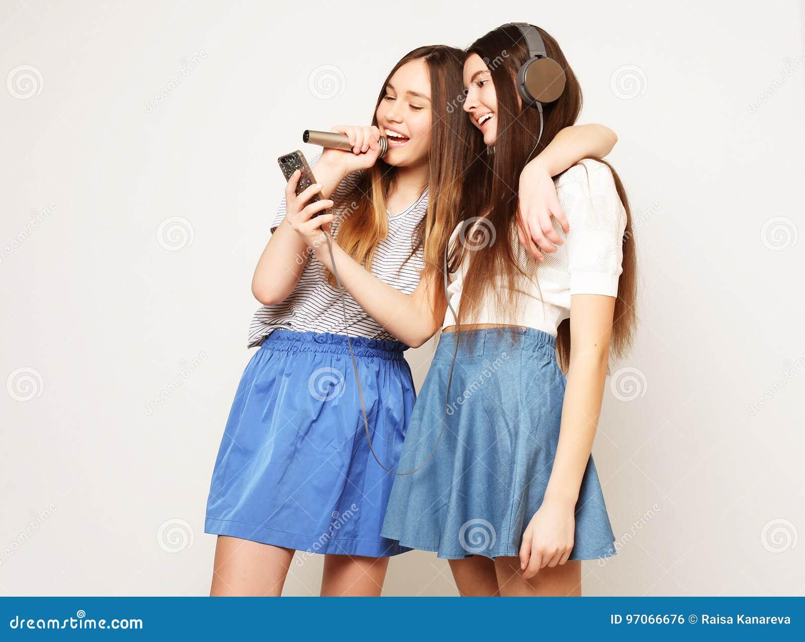 As meninas do moderno da beleza com um microfone que cantam e tomam a imagem