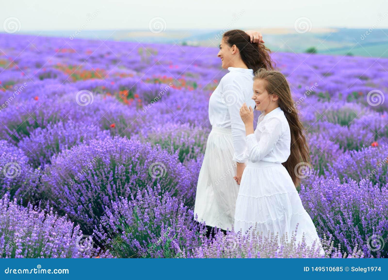 As meninas est?o no campo de flor da alfazema, paisagem bonita do ver?o