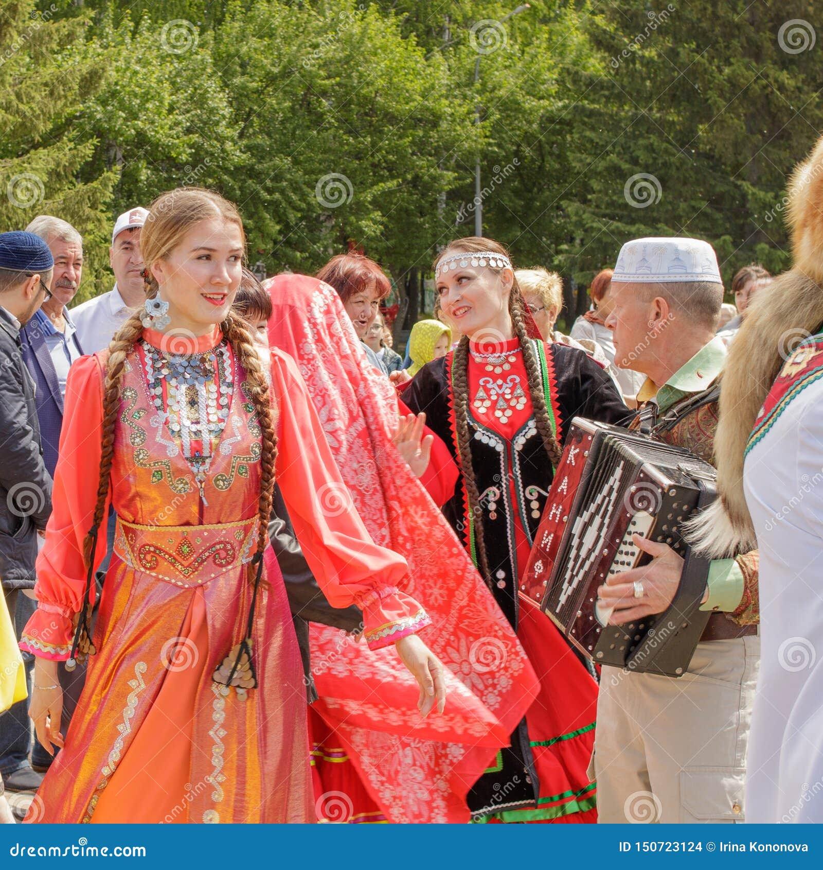 As meninas na roupa nacional Tatar estão dançando sob o acordeão do botão