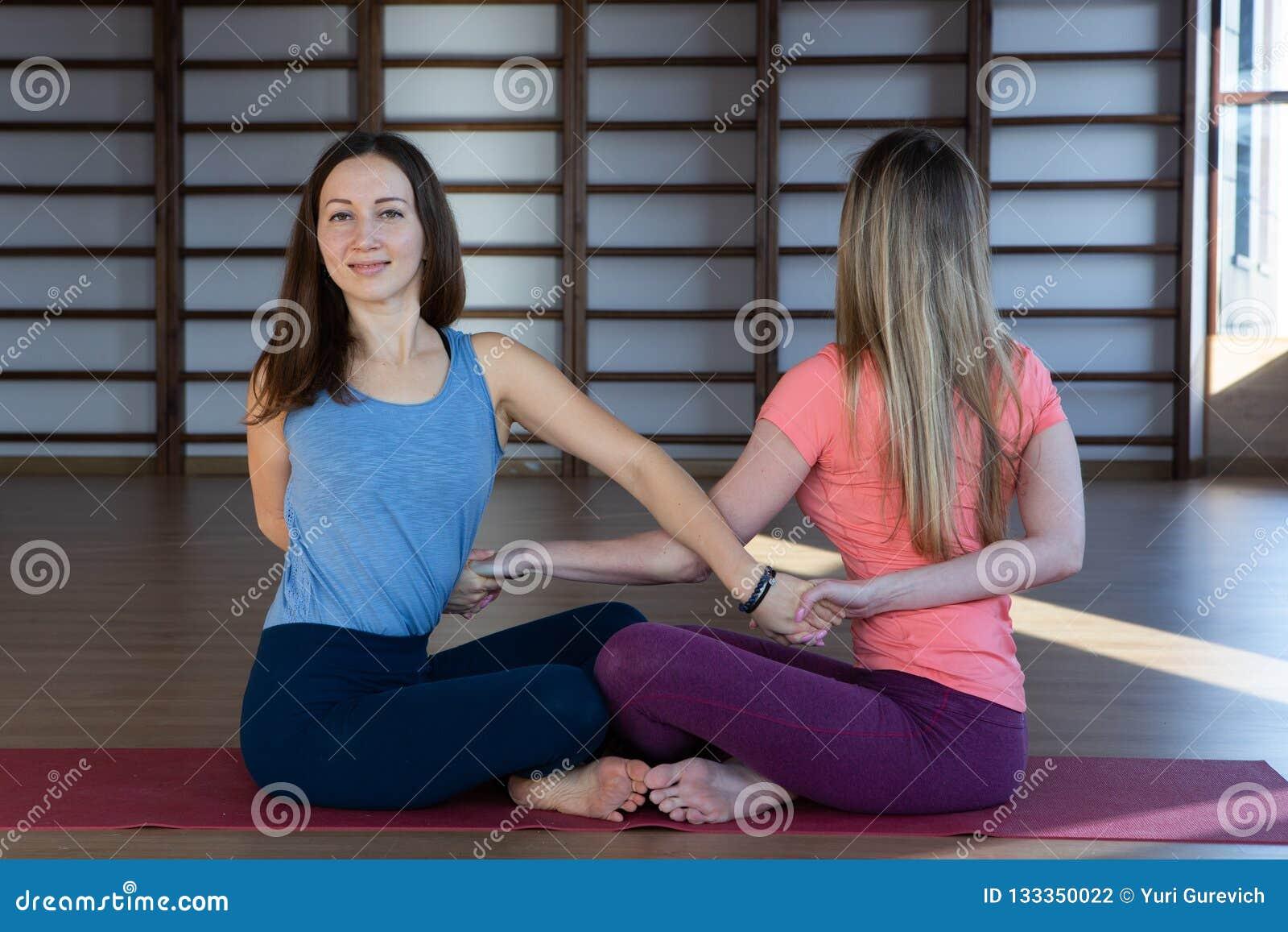 As meninas novas atrativas do esporte estão fazendo a ioga junto treinamento do grupo