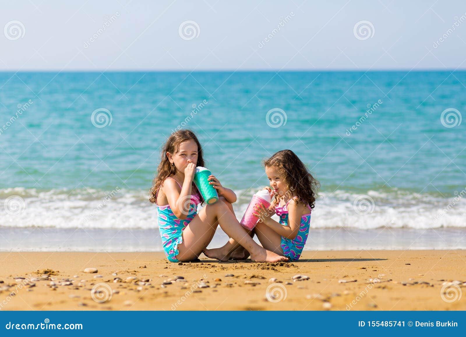 As meninas sentam-se para sentar-se oposto a se e para beber do conceito bonito colorido das férias em família dos vidros de cock