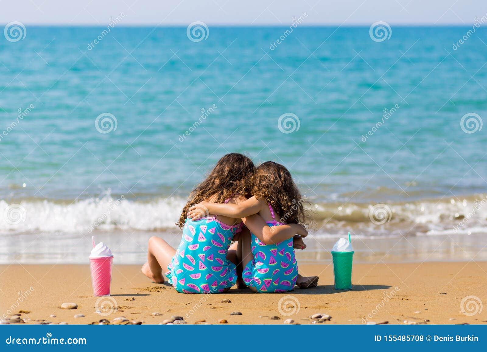 As meninas sentam-se para trás na areia e no afago, junto com cocktail Conceito das f?rias em fam?lia Irm?s felizes