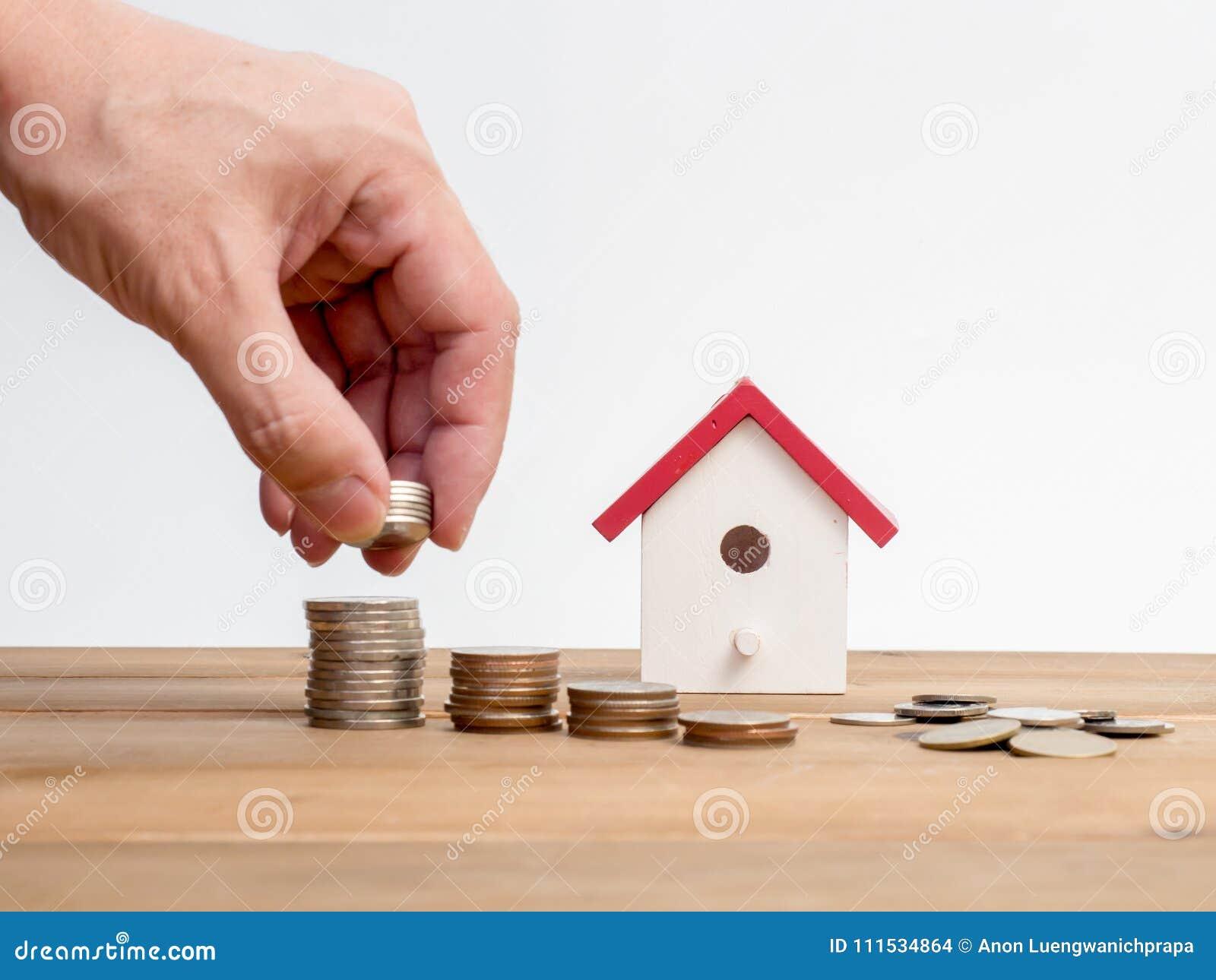 As moedas do dinheiro empilham o crescimento com a casa vermelha no fundo de madeira Investimento do crescimento do negócio e ide