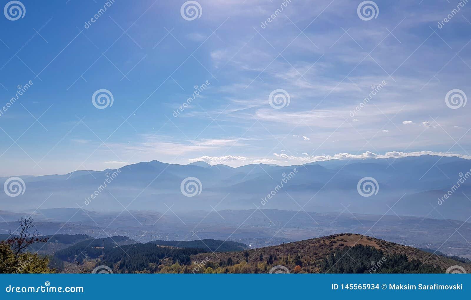 As montanhas mostram em silhueta através da névoa com horizonte bonito