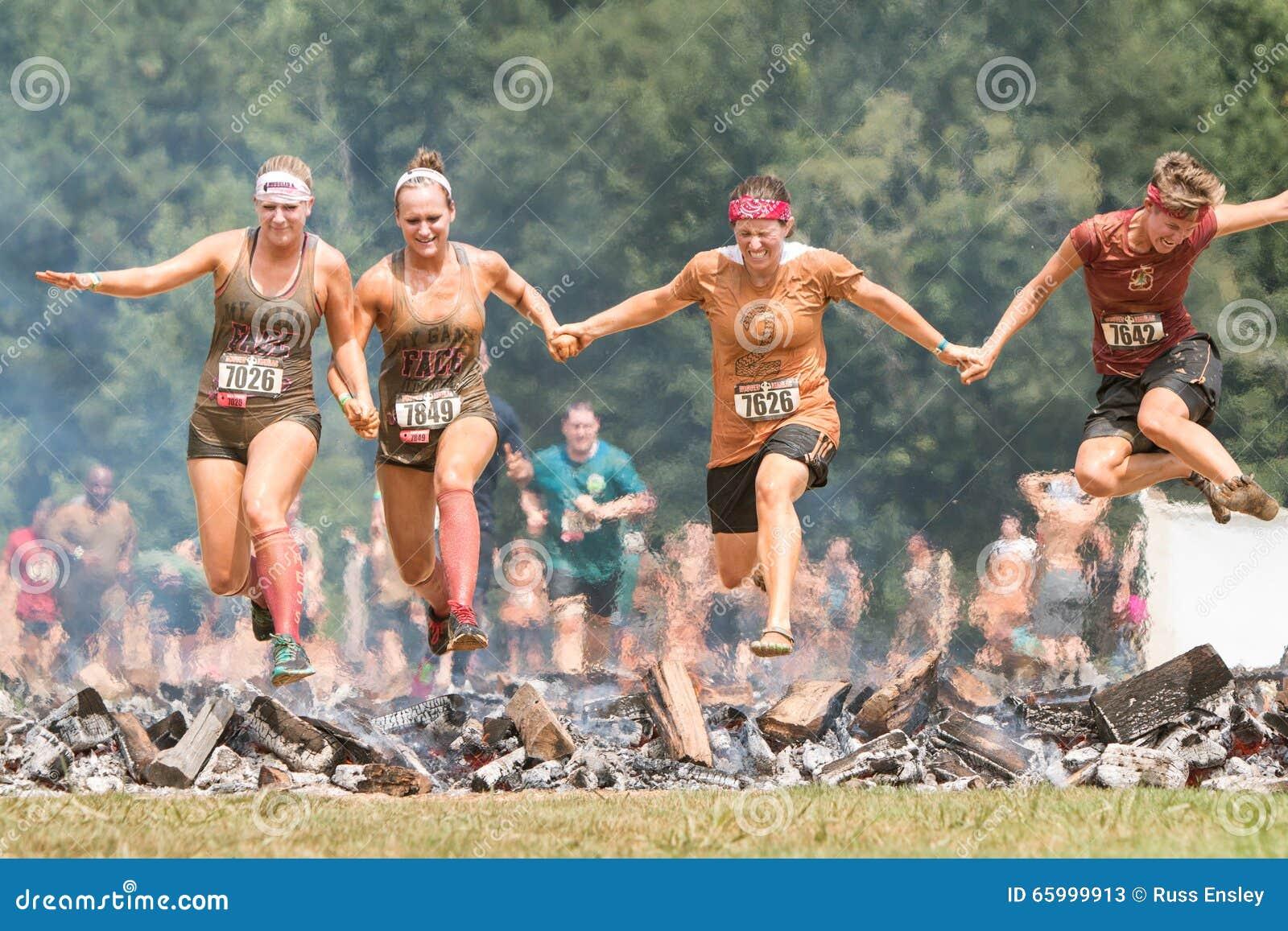 As mulheres cerc logs ardentes junto na raça extrema do curso de obstáculo