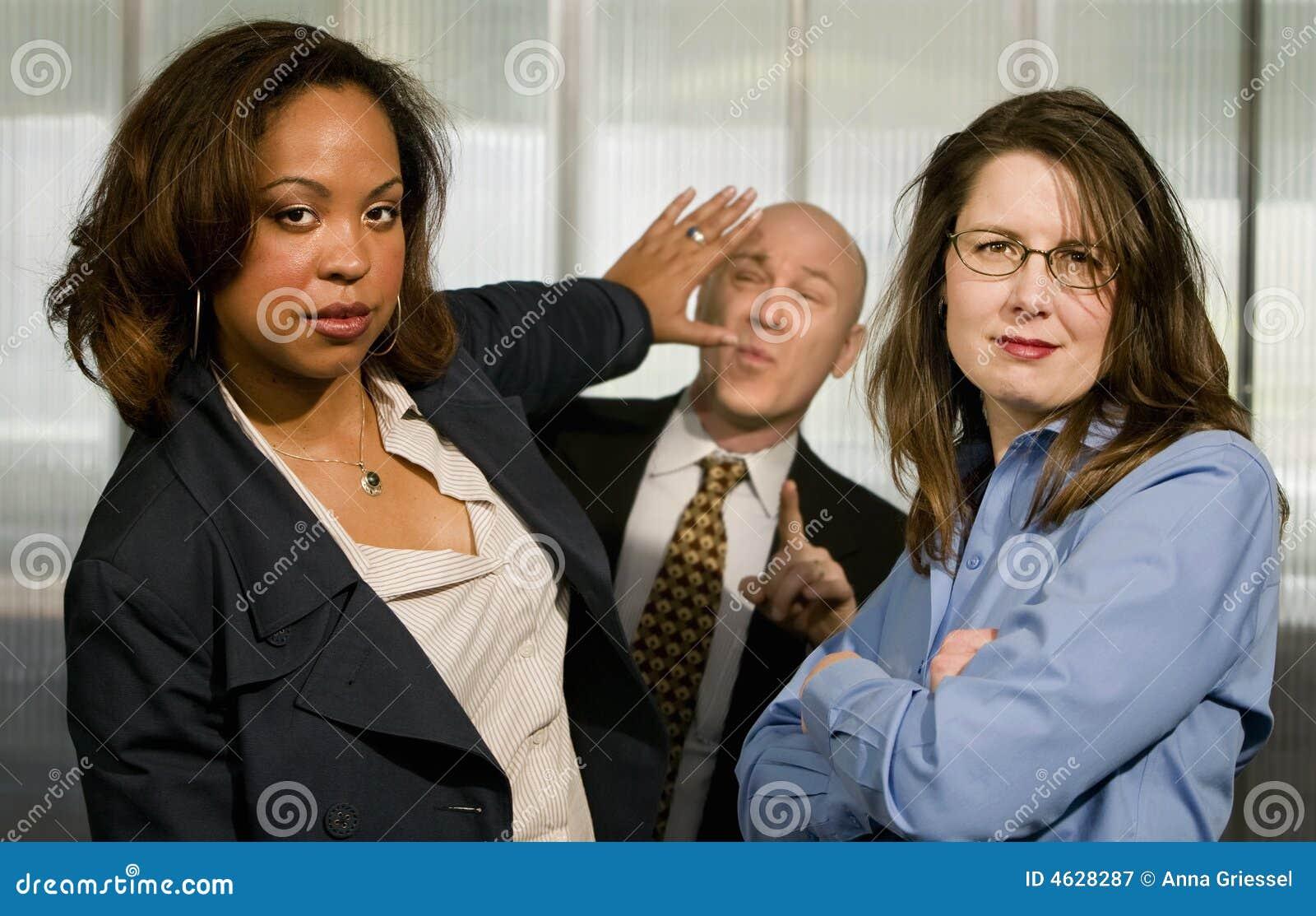 As mulheres de negócios empurram para trás um homem de negócios