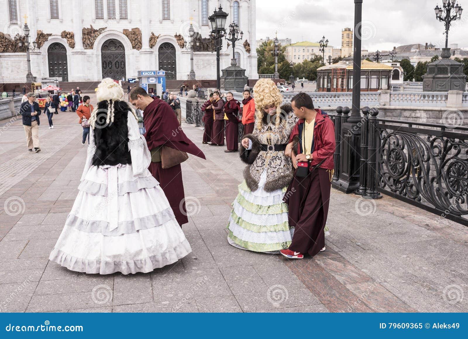 As mulheres de Roma em vestidos antigos fazem um tolo de monges tibetanas em t