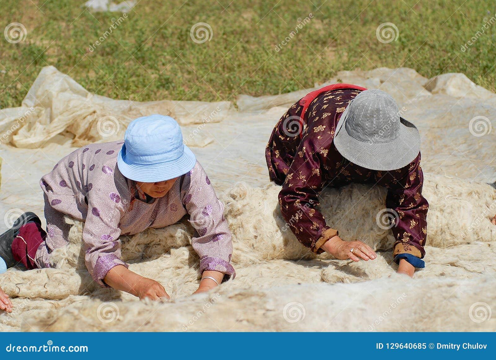 As mulheres Mongolian superiores produzem o feltro em Harhorin, Mongólia