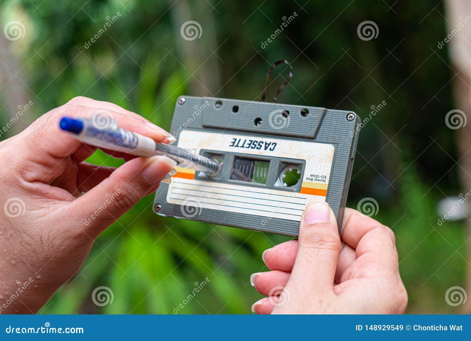 As mulheres rebobinam um vintage compacto da cassete de banda magn?tica no fundo do borr?o