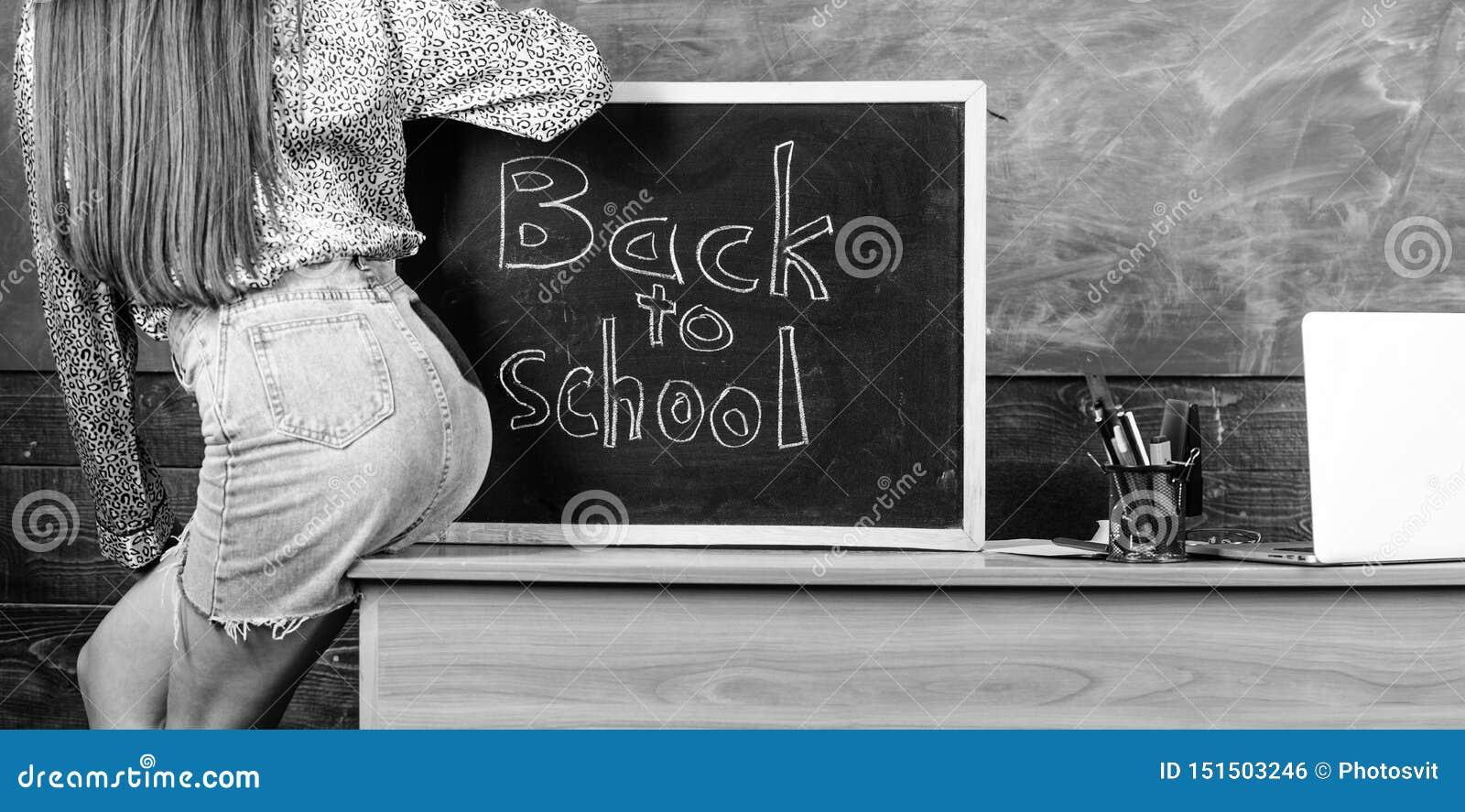 As n?degas  sexy  da mini saia do professor estudante sentam a inscri??o do quadro-negro da tabela de volta ? escola Quebra da sa