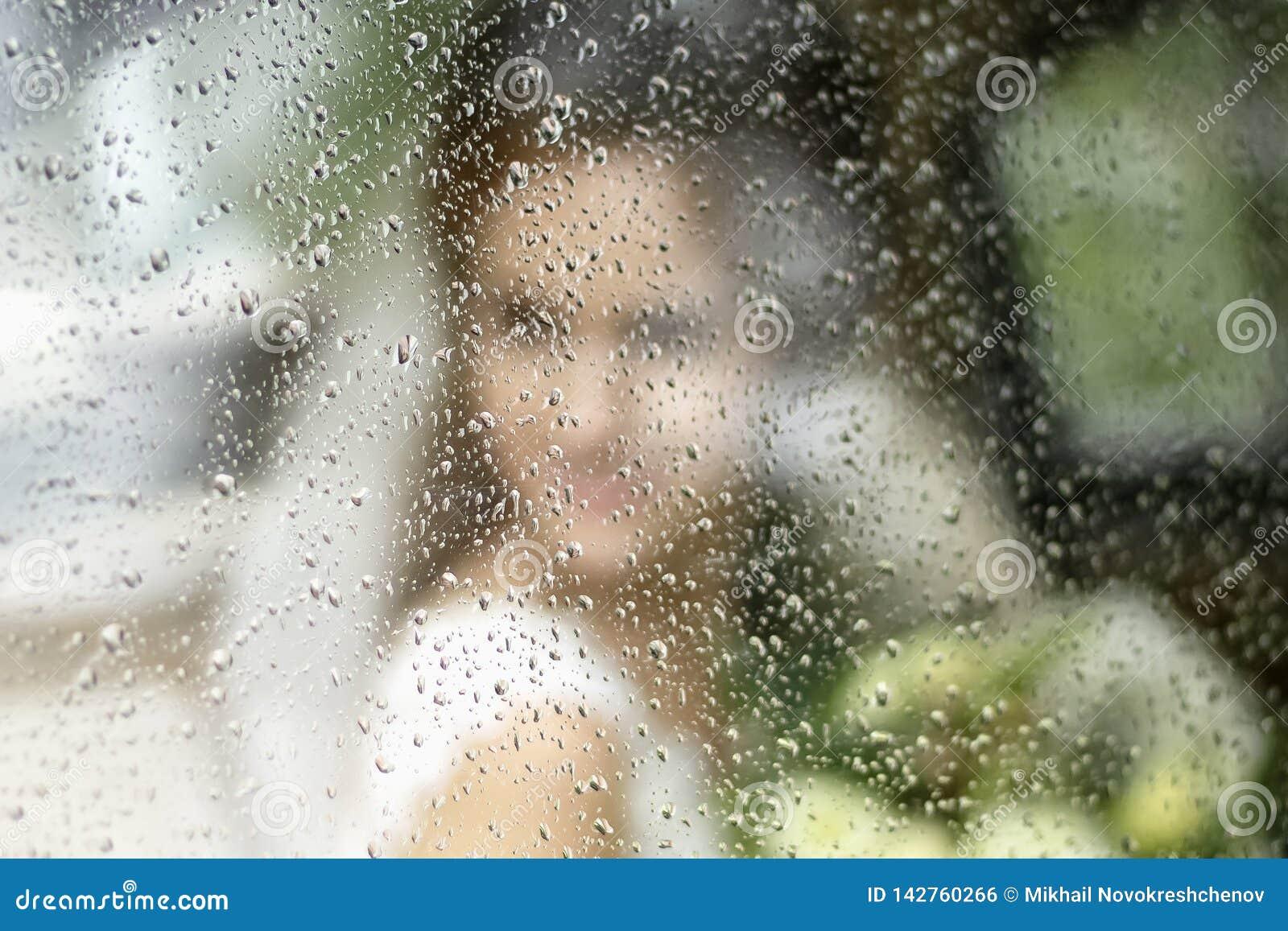 As noivas mostram em silhueta em um vestido de casamento com um ramalhete das flores através do vidro em gotas da chuva
