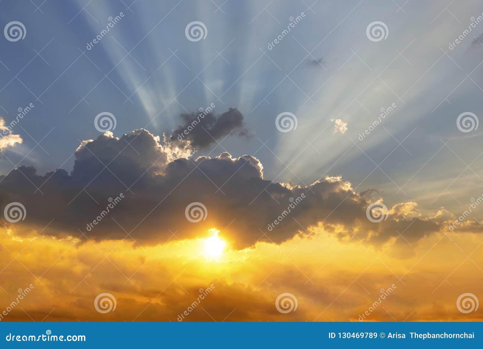 As nuvens e o sol brilham através dos raios de luz no p iluminado