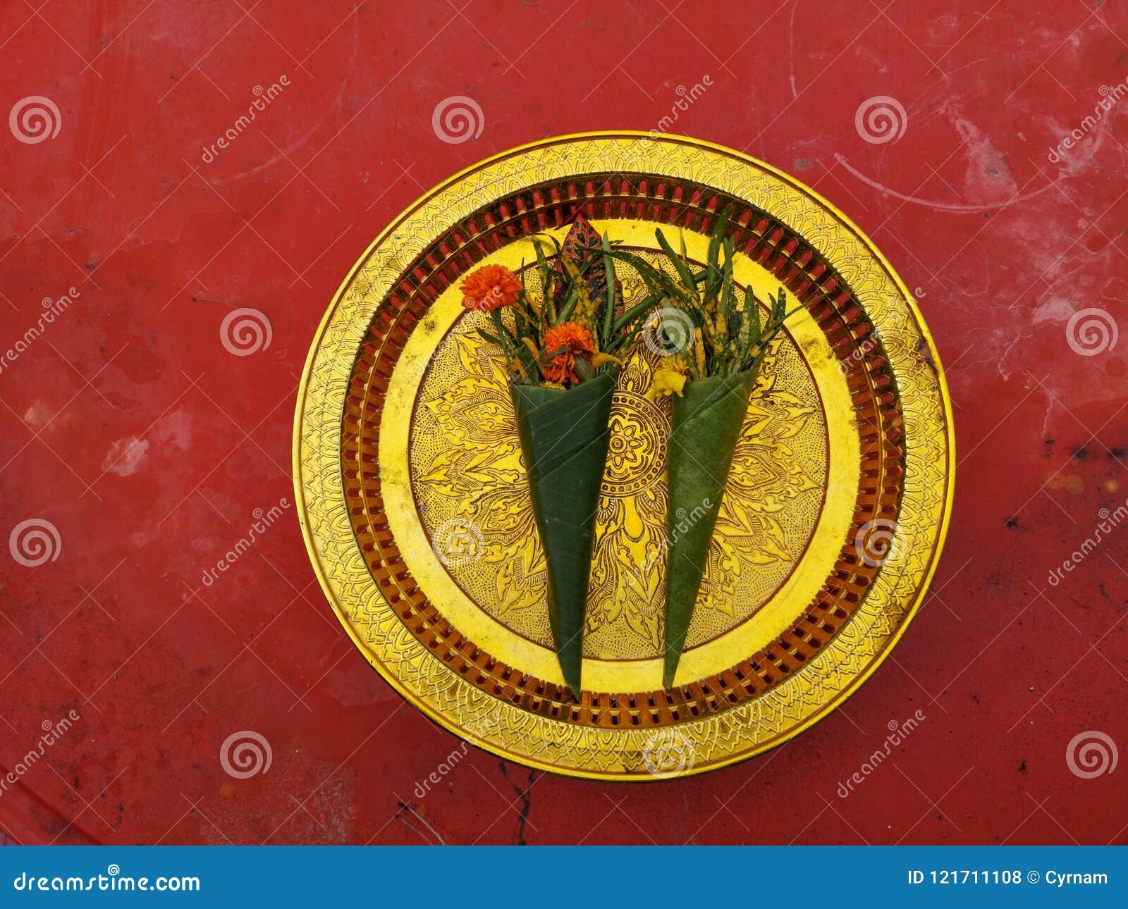 As ofertas à deusa, flores envolvidas na folha da banana ofereceram à Buda na placa dourada com fundo vermelho