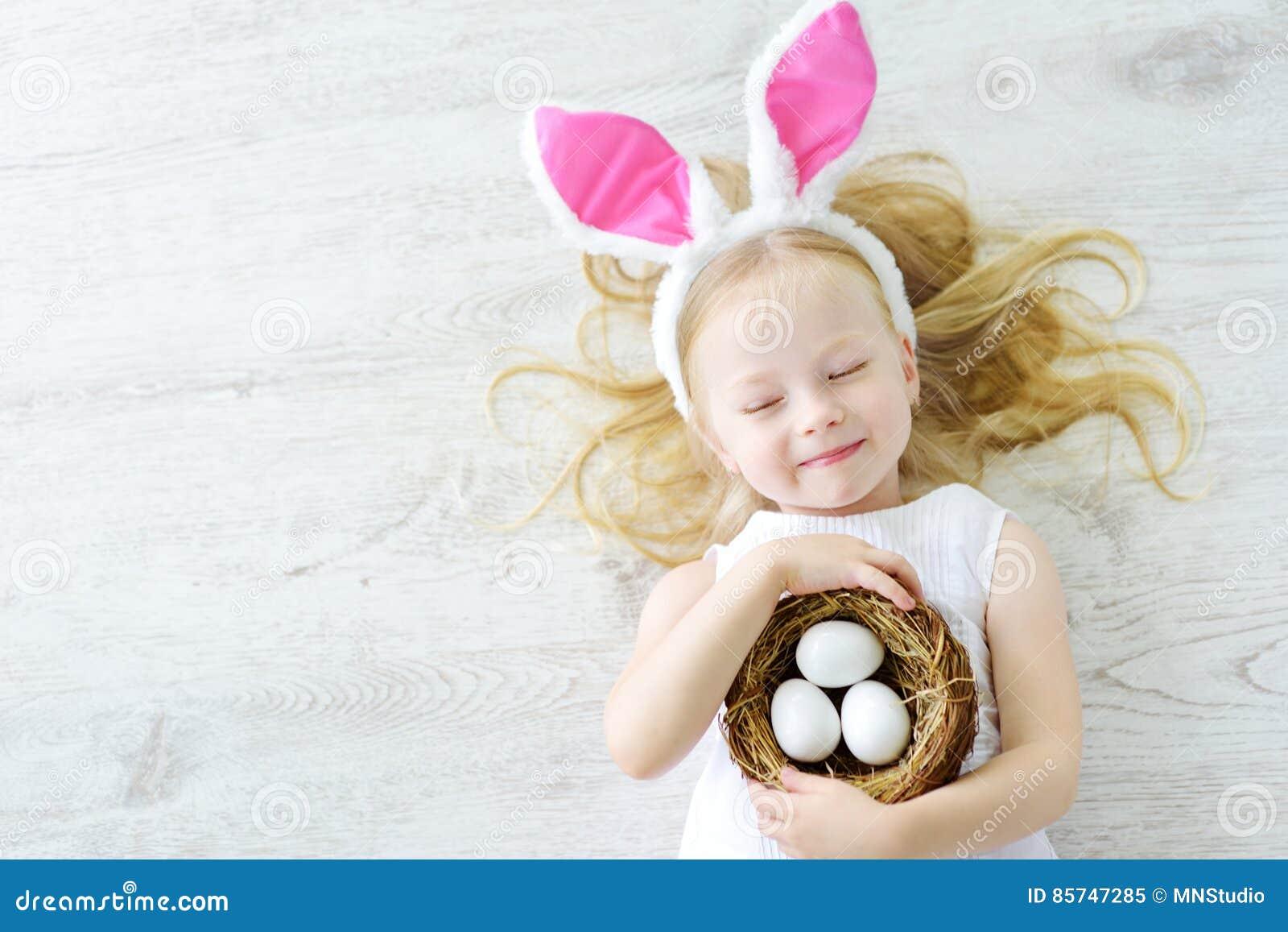 As orelhas vestindo do coelho da menina bonito que jogam o ovo caçam na Páscoa