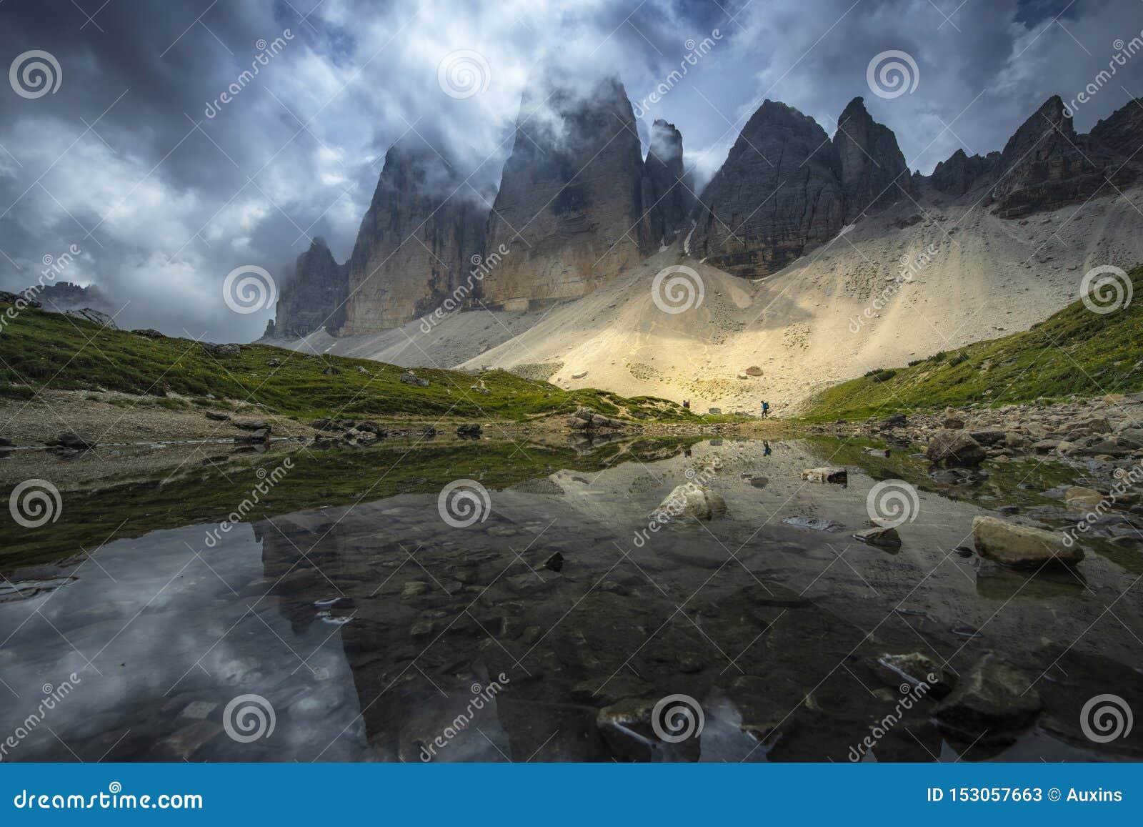 As paisagens bonitas ideia da reflexão da montanha no rio com o céu azul no verão de Tre Cime, dolomites, Itália