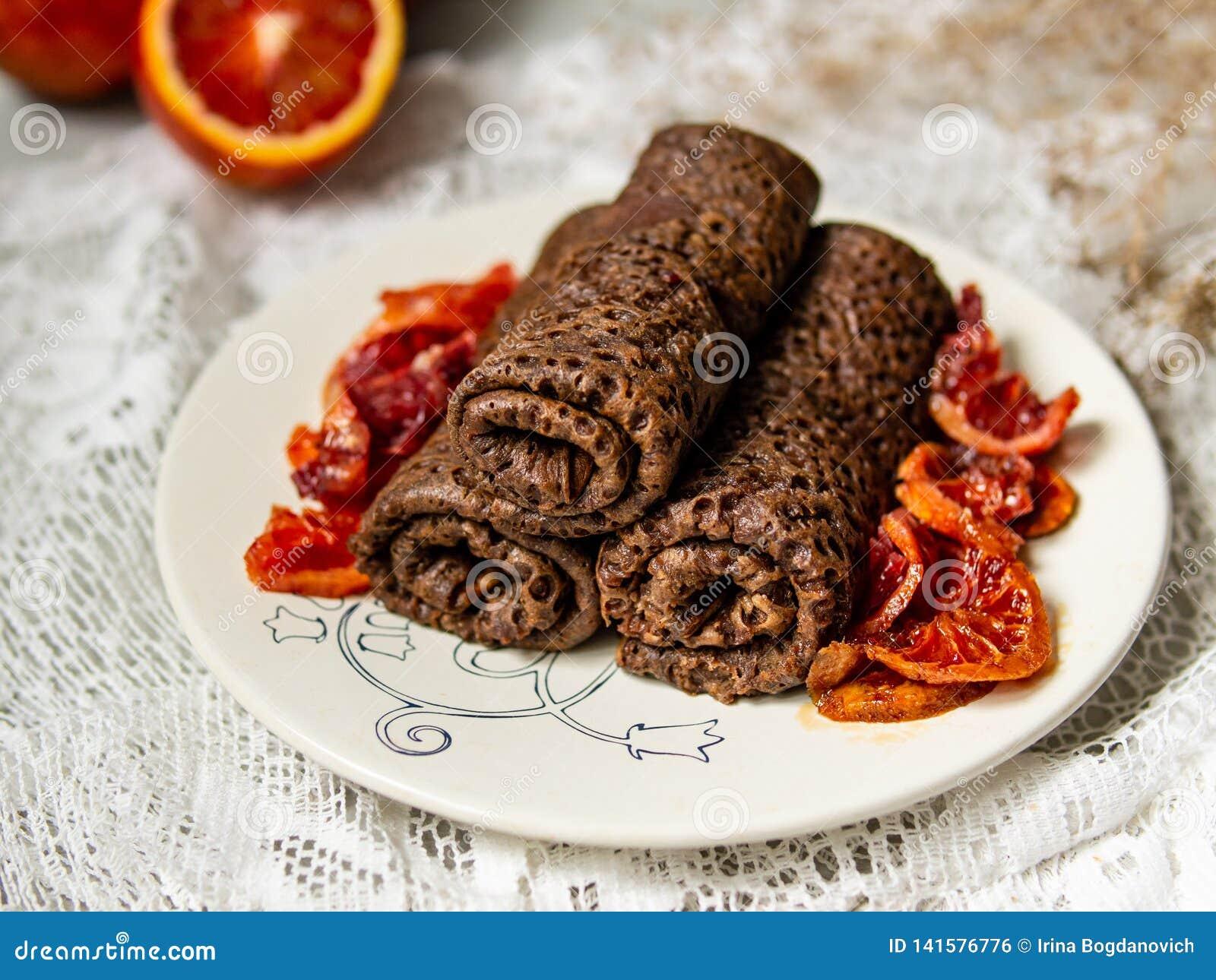 As panquecas finas do chocolate rolaram em um tubo com molho das laranjas pigmentadas em uma placa branca Pilha de crepes, blin d