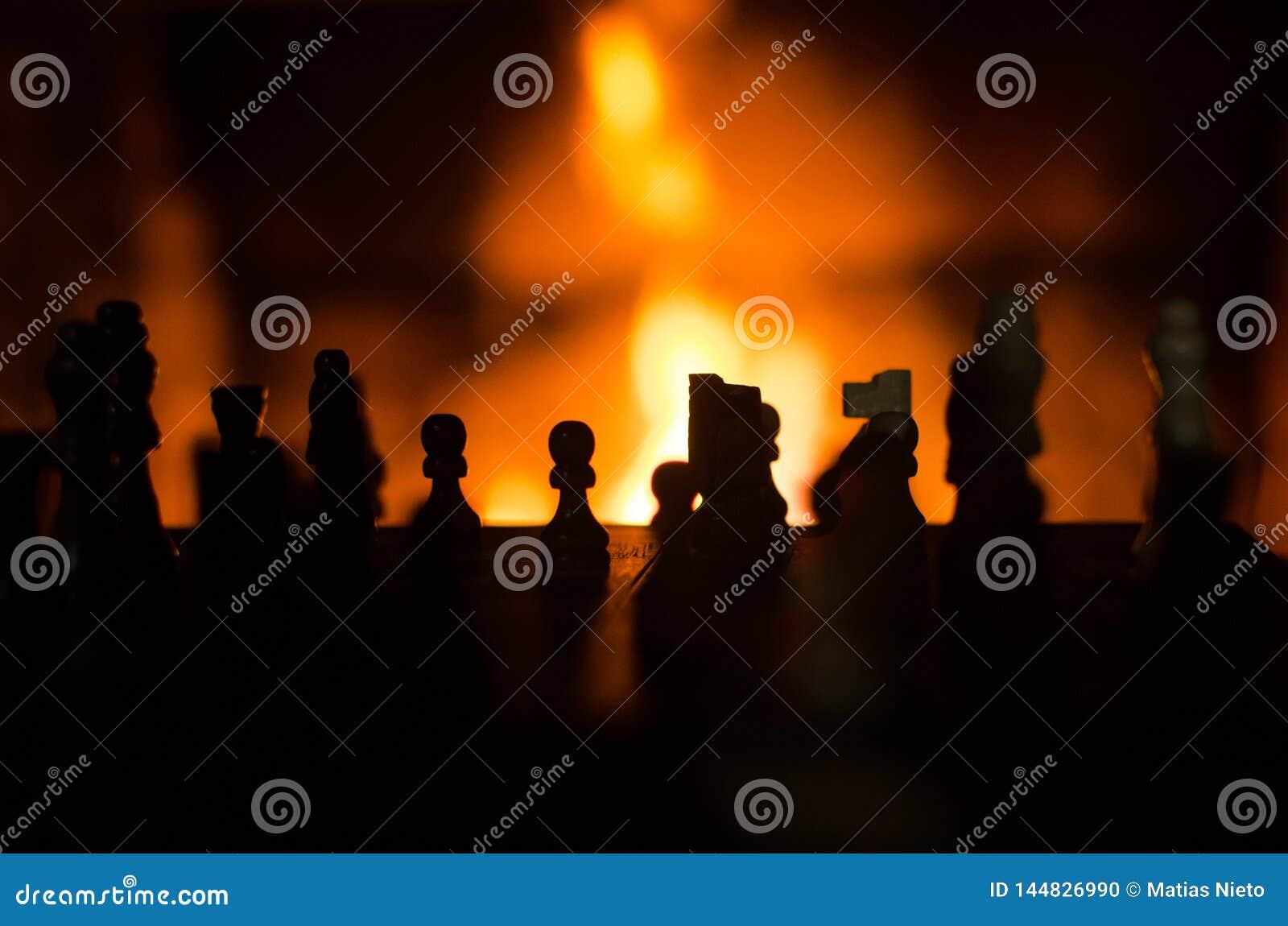 As partes de xadrez mostram em silhueta retroiluminado pela chaminé