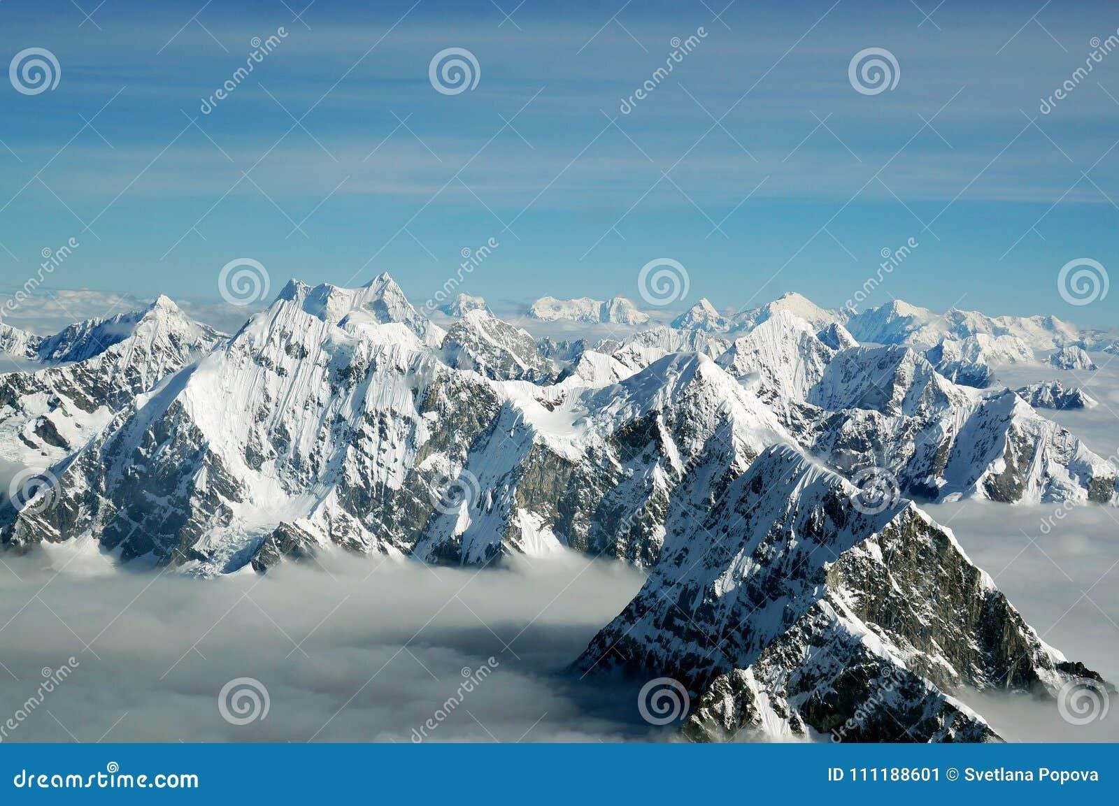 As partes superiores das montanhas Himalaias acima das nuvens, vista do avião nepal
