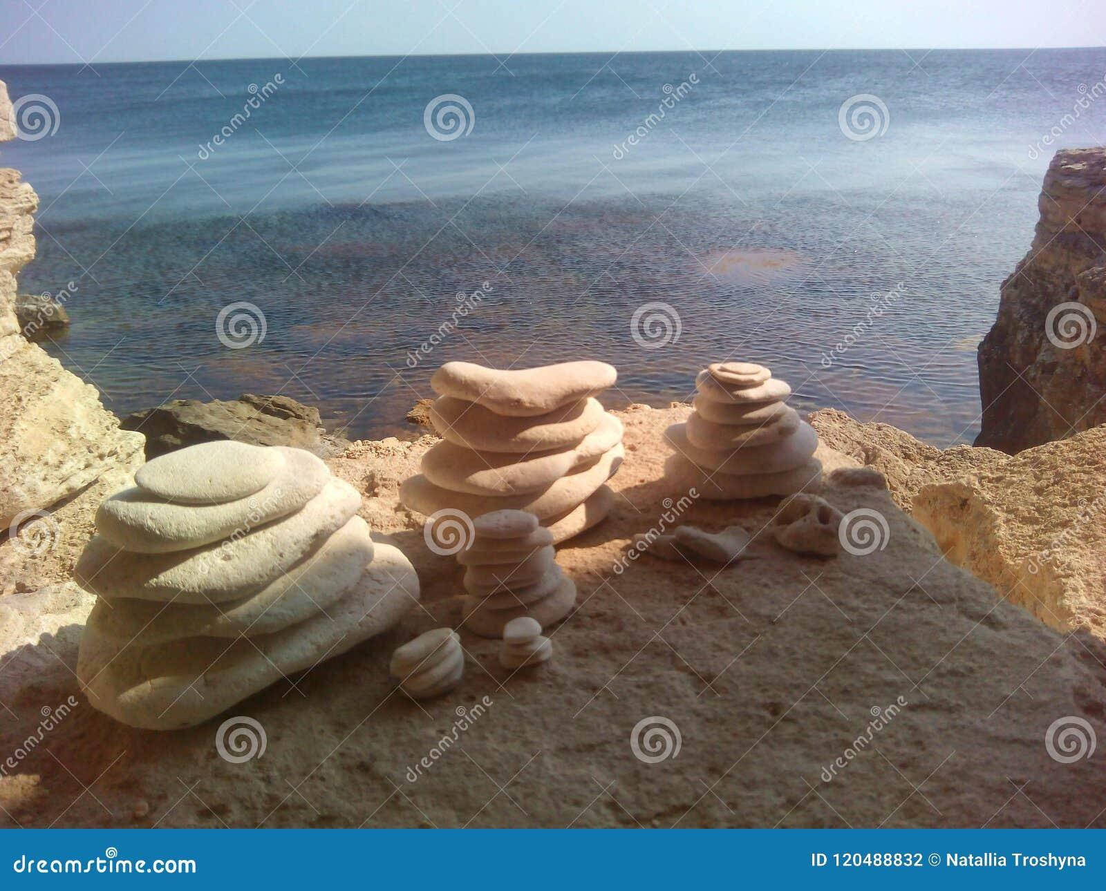 As pedras bonitas equilibram em um fundo da rocha da pedra do mar