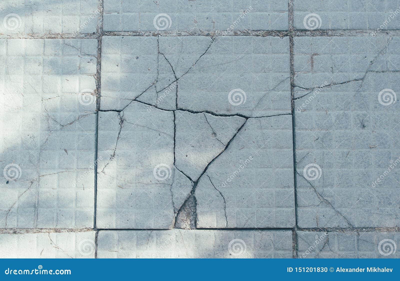 As pedras de pavimentação rachadas cinzentas