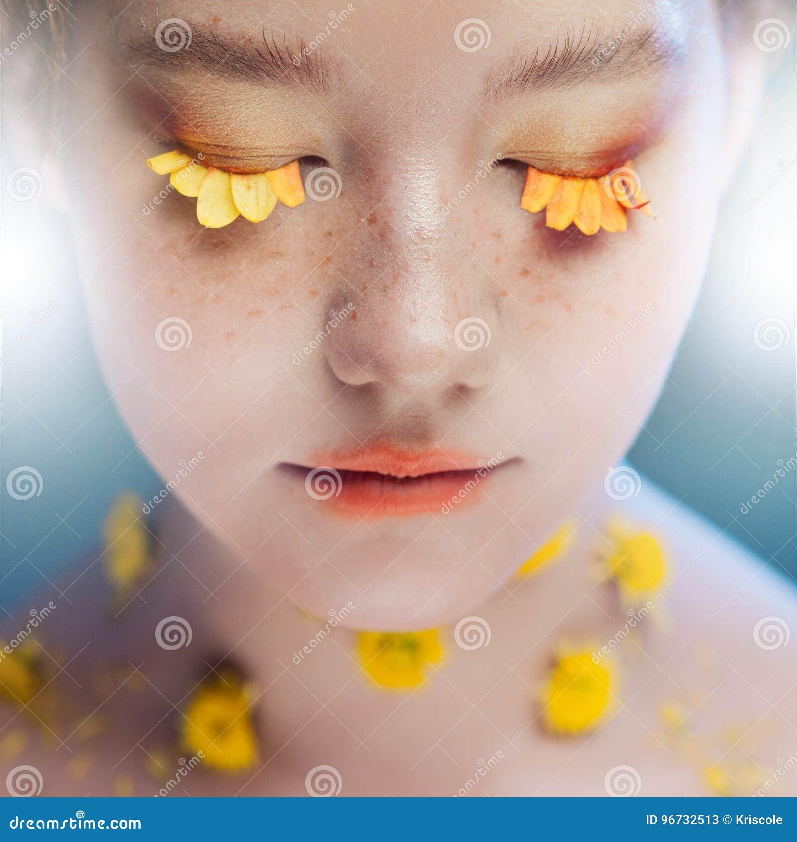 As pestanas gostam das pétalas das flores Moça bonita na imagem da flora, retrato do close-up