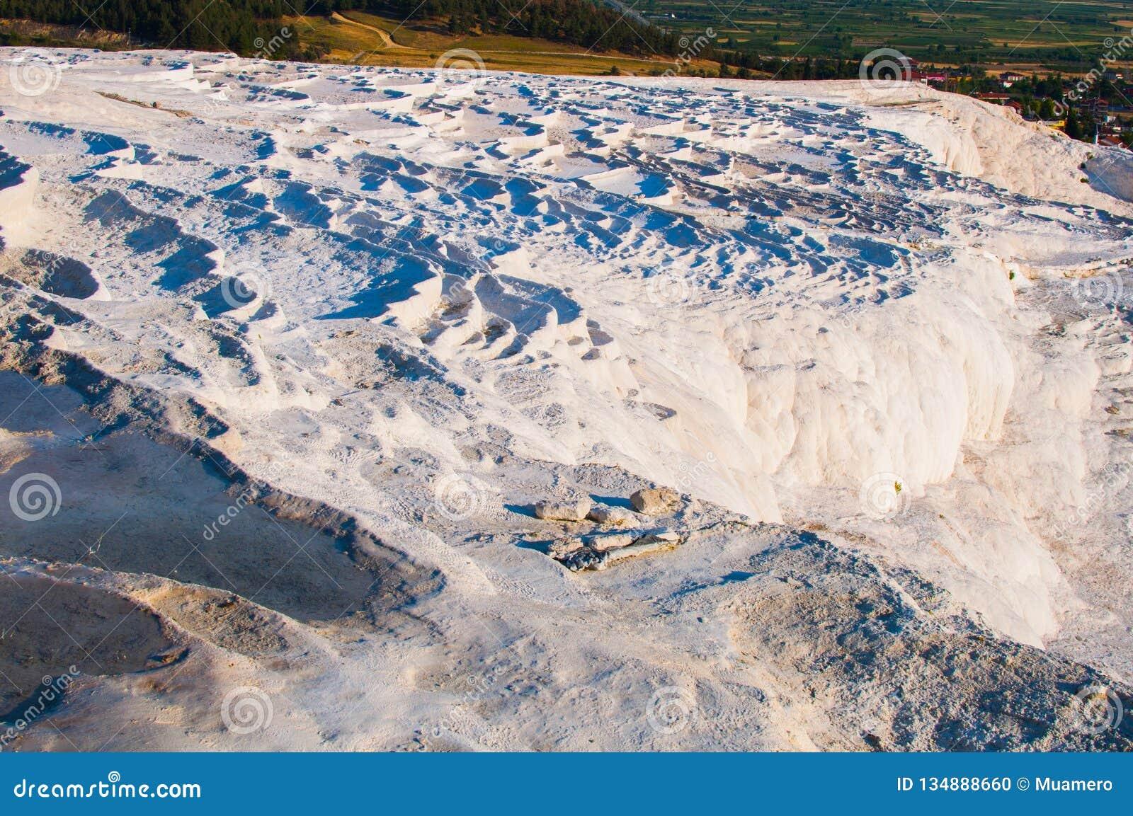 As piscinas pequenas completas da água nas rochas brancas feitas do carbonato de cálcio