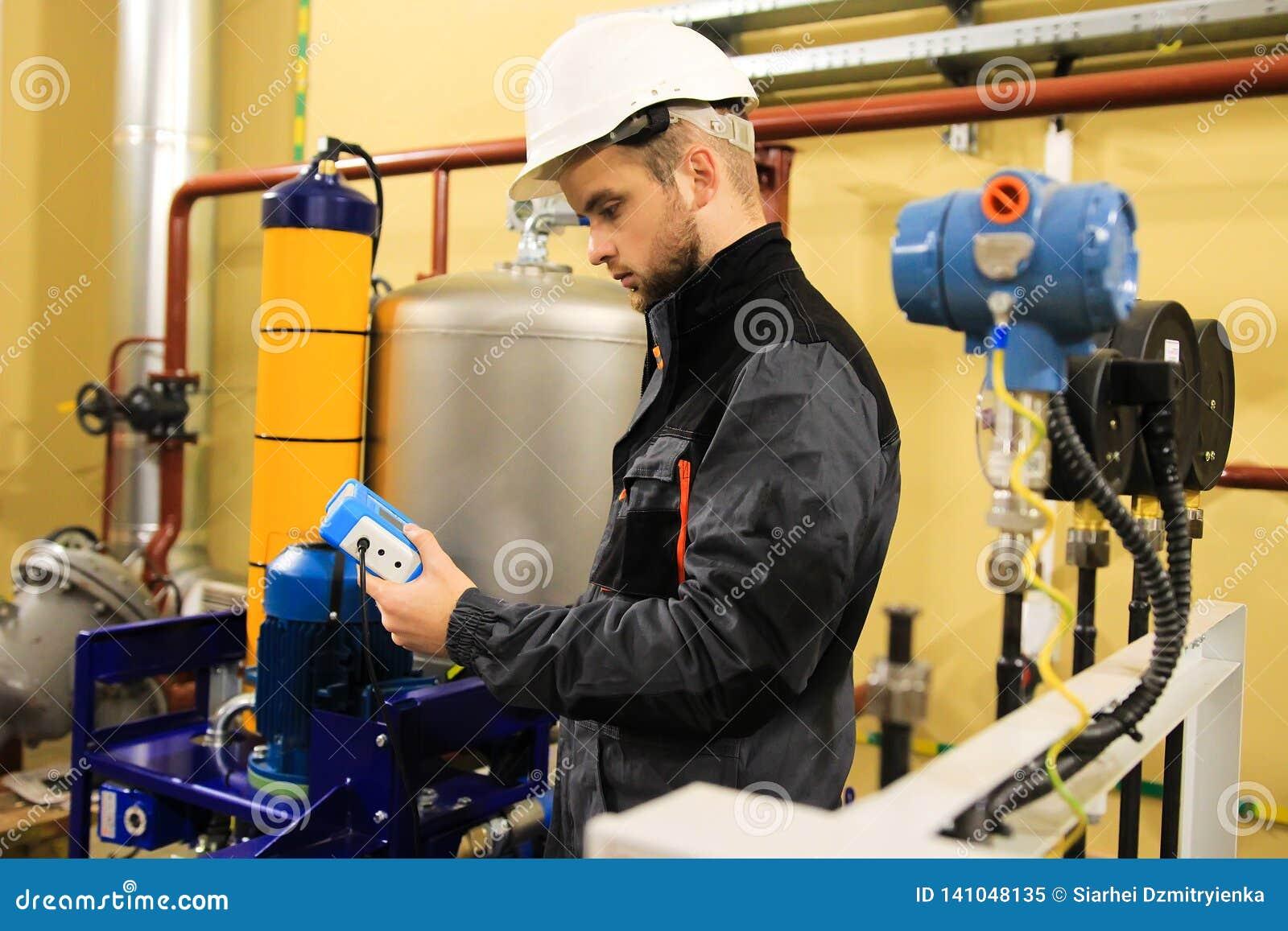As pontas de prova cheking do coordenador do técnico exercem pressão sobre sensores na planta de refinaria industrial do poder