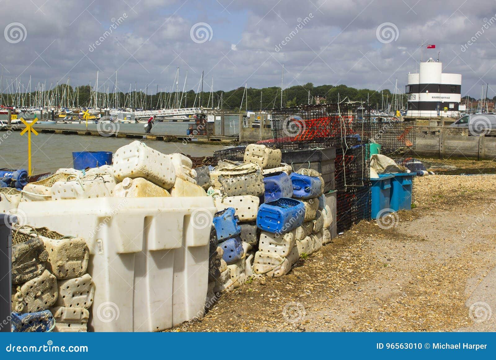 As redes de pesca comercial e as caixas plásticas rejeitaram no cais em Warsash na costa sul PF Inglaterra em Hampshire