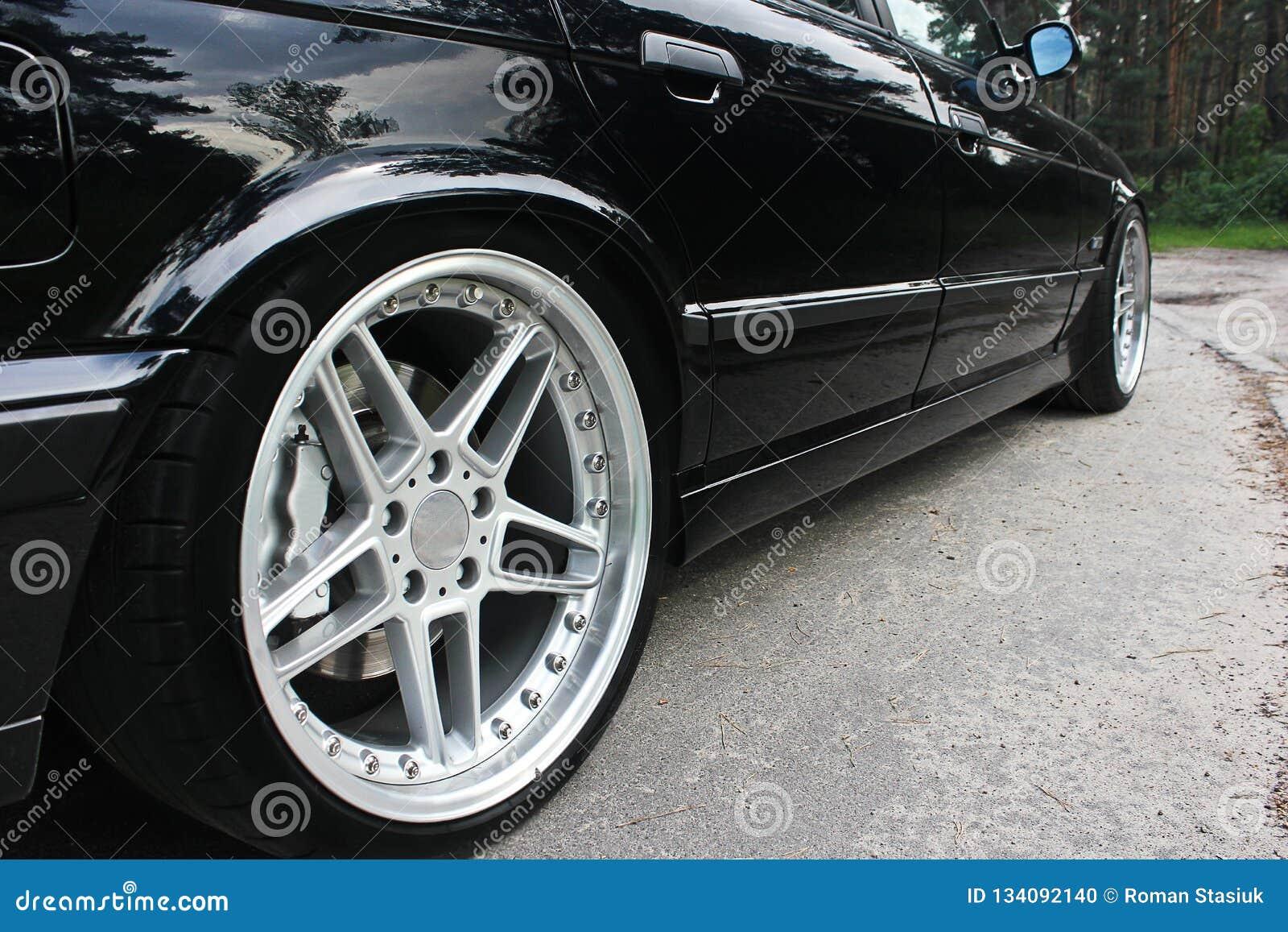 As rodas de carro fecham-se acima em um fundo do asfalto Pneus de carro Close-up da roda de carro