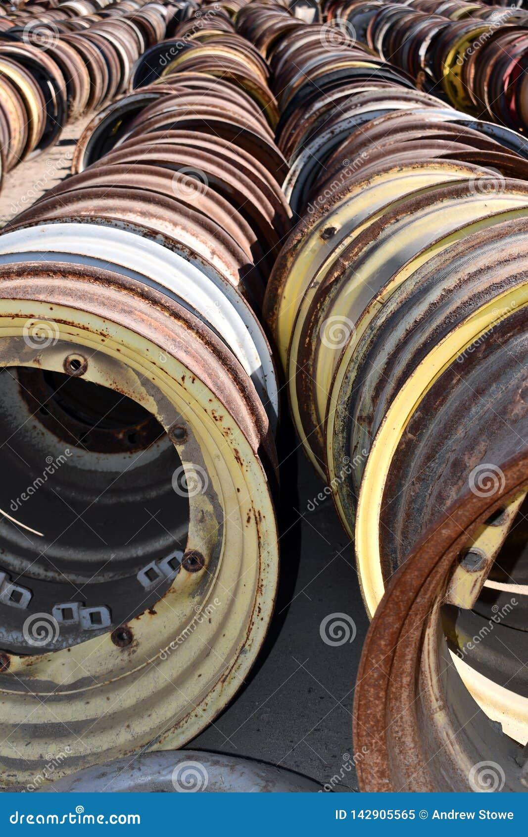 As rodas e as bordas de aço de tratores e da maquinaria velhos do vintage estão nas fileiras encontradas em um campo