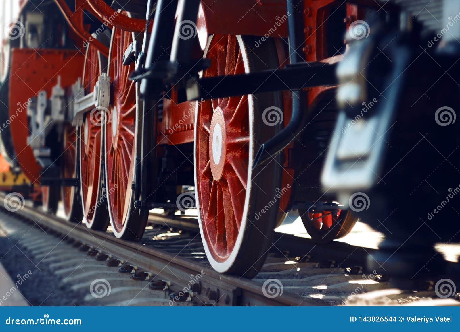 As rodas vermelhas de uma locomotiva de vapor velha do vintage