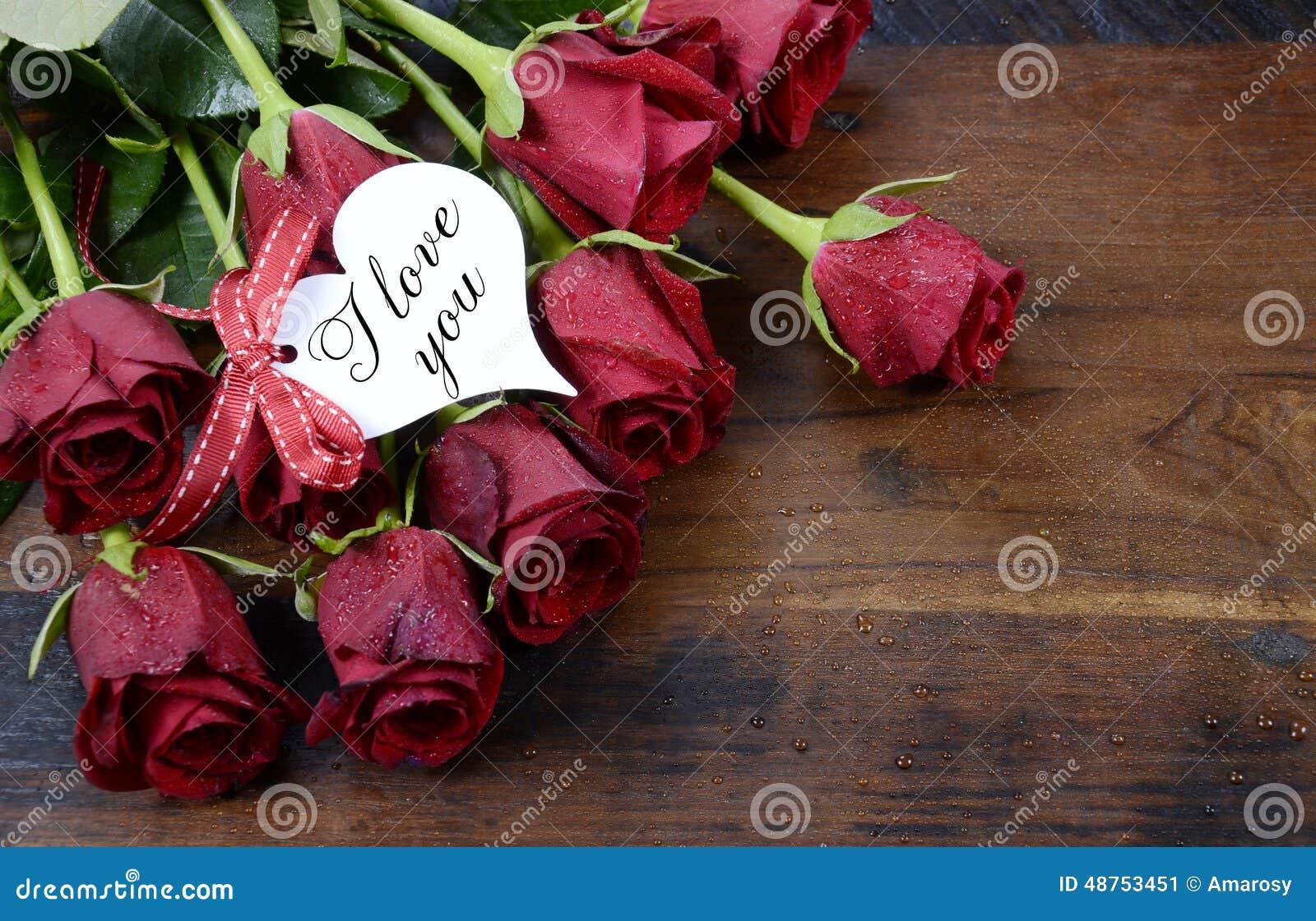 As rosas vermelhas de dia de Valentim na obscuridade reciclaram o fundo de madeira