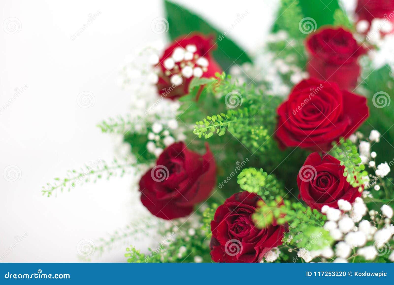 As rosas vermelhas do ramalhete das flores no fundo branco agradecem a lhe e ao cartão do amor