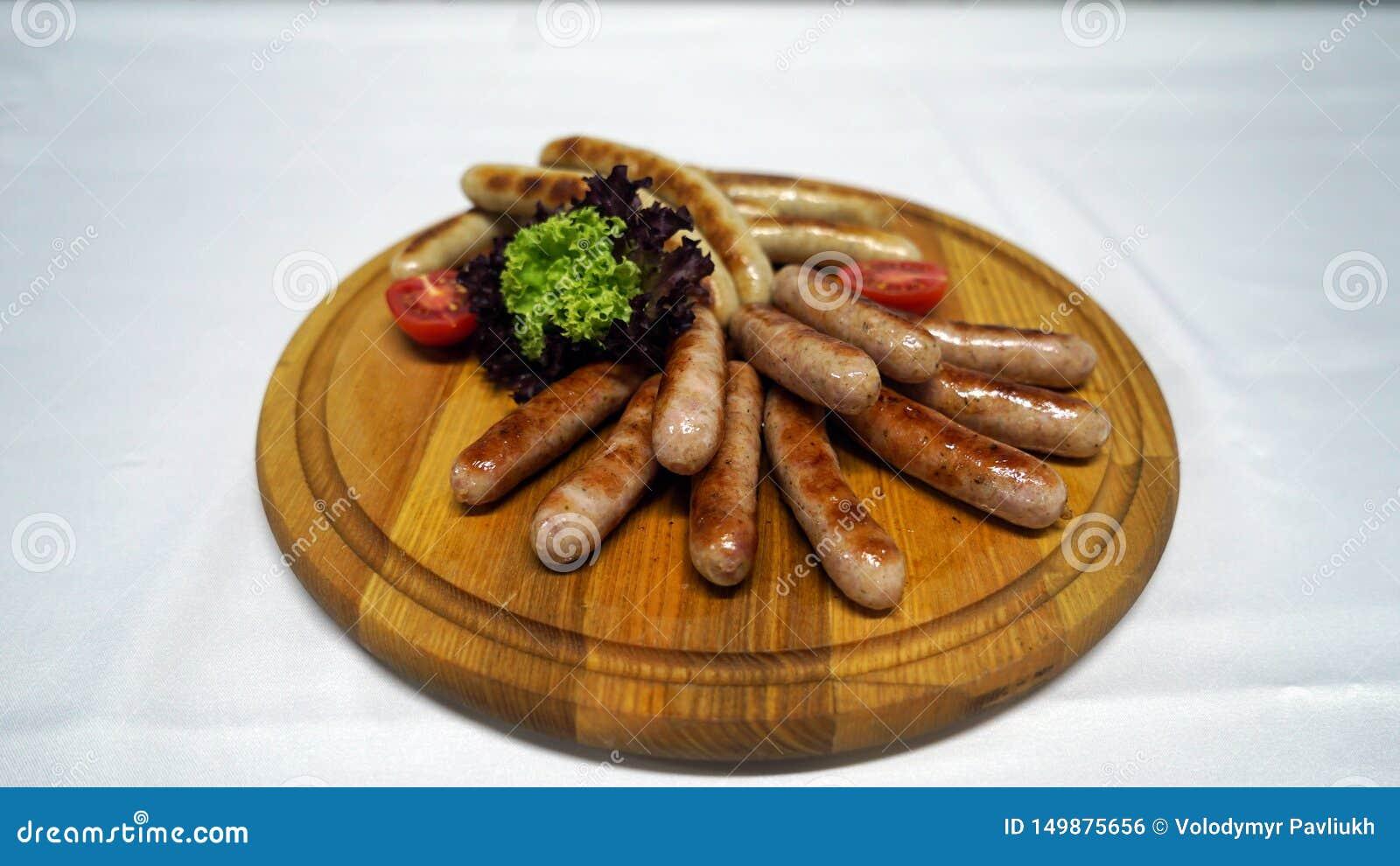 As salsichas suculentas cozinharam em uma grade, crosta cozida e serviram com os legumes frescos na madeira