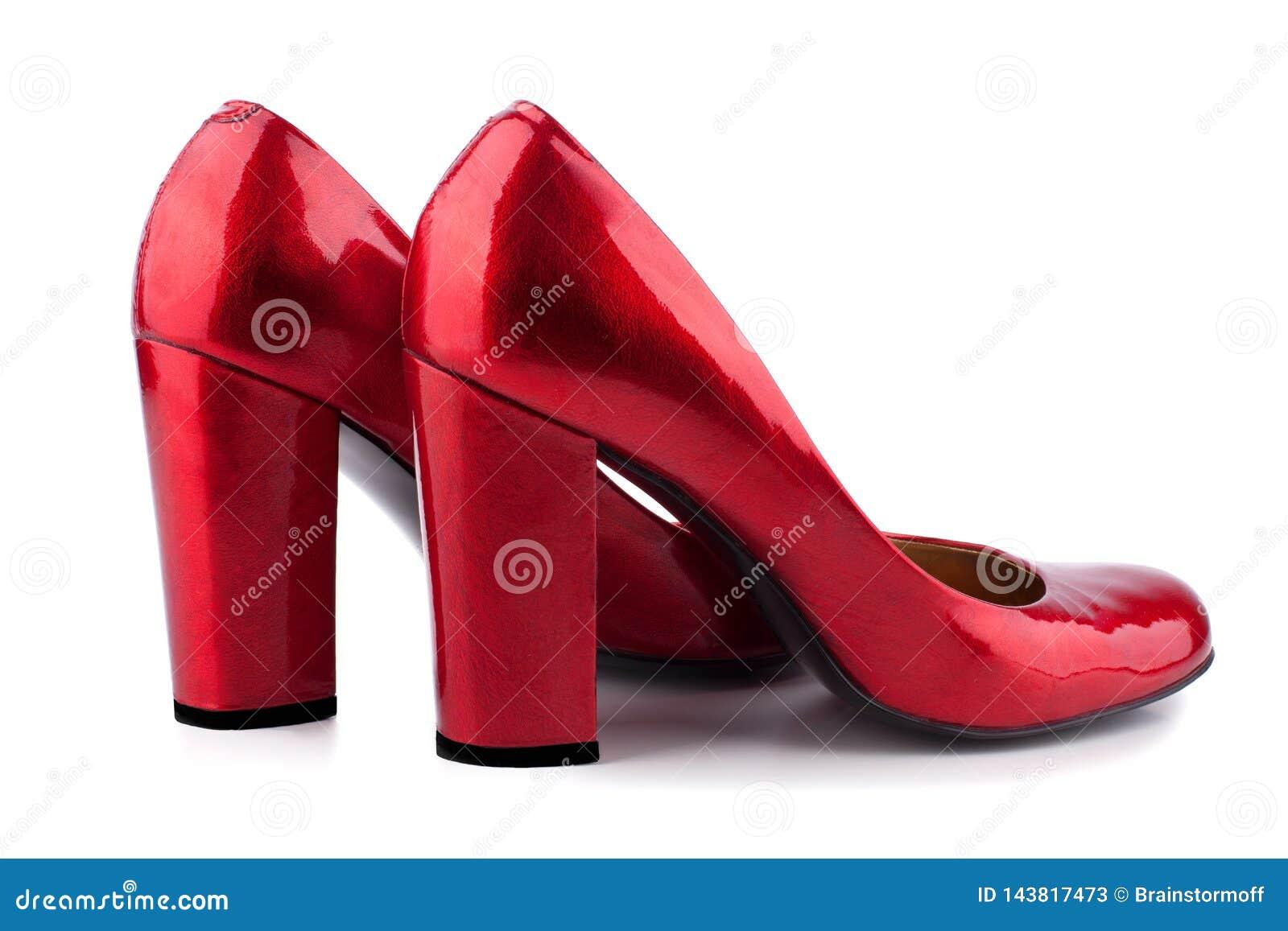 As sapatas das mulheres vermelhas com os saltos altos feitos da vista lateral de couro envernizada em um fim branco do fundo acim