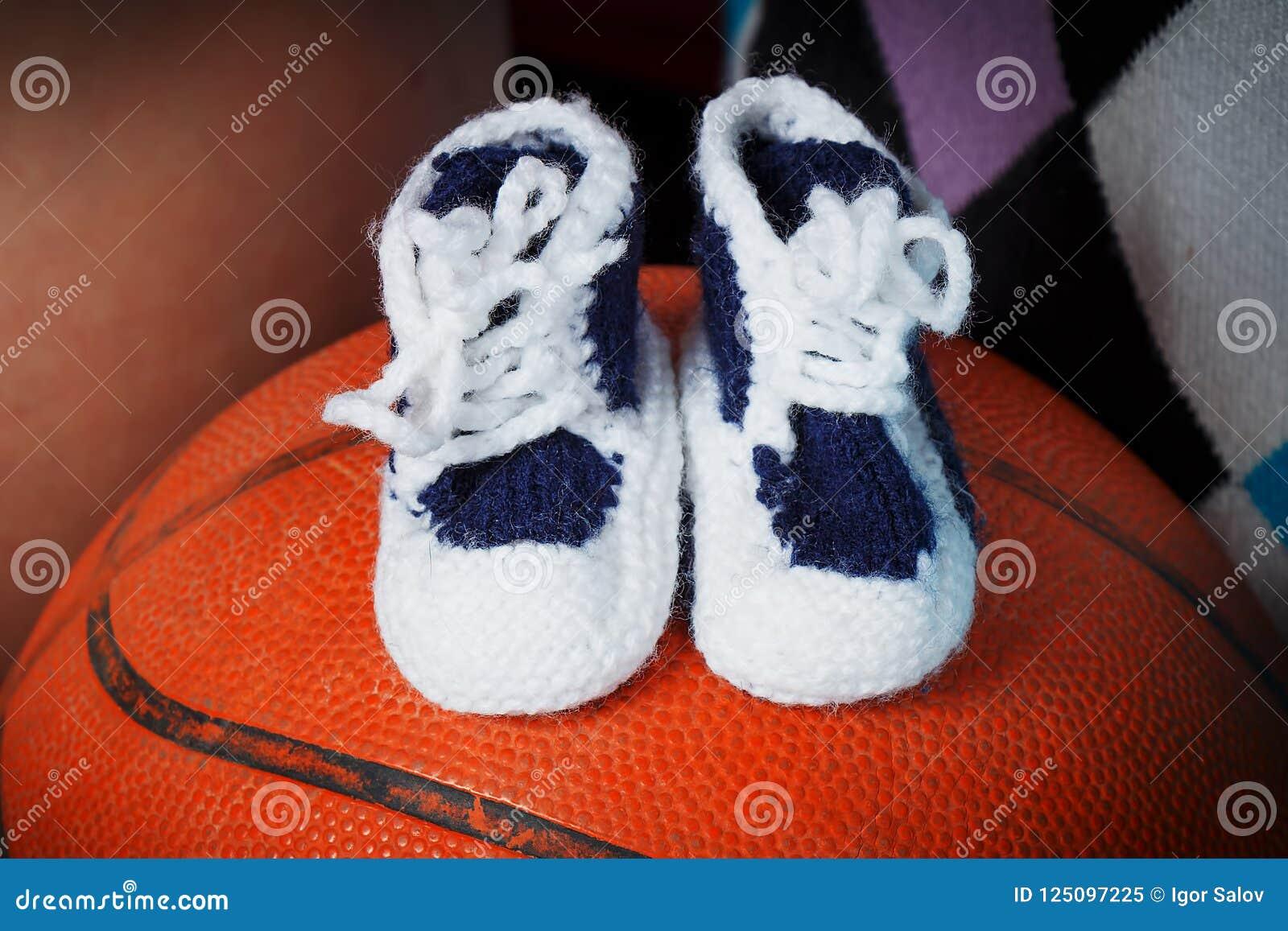 As sapatas de bebê estão em uma bola da cesta