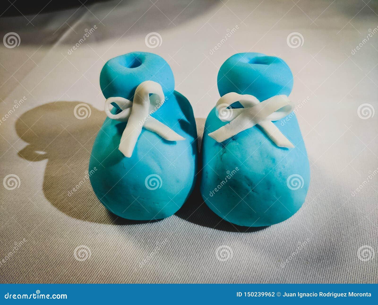 As sapatas de bebê fizeram do açúcar