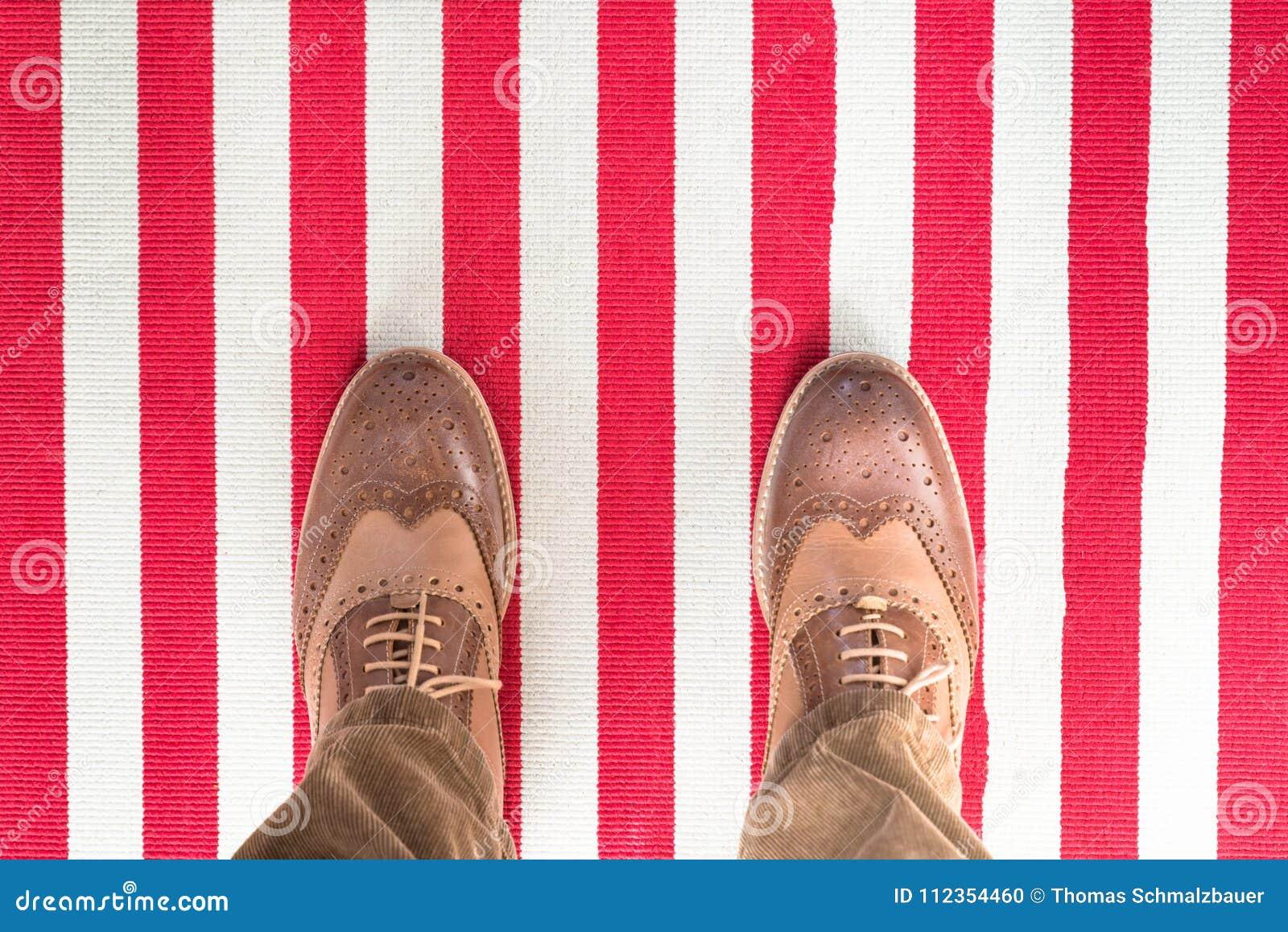 As sapatas do negócio em um branco vermelho listraram carped