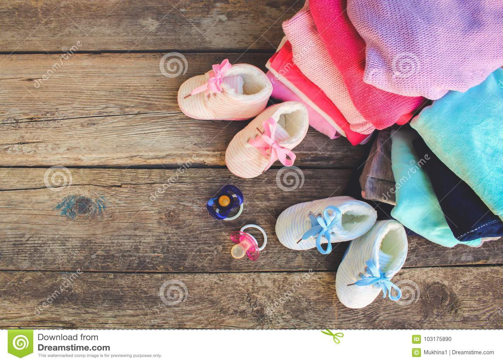 As sapatas, a roupa e as chupetas de bebê picam e azul no fundo de madeira velho