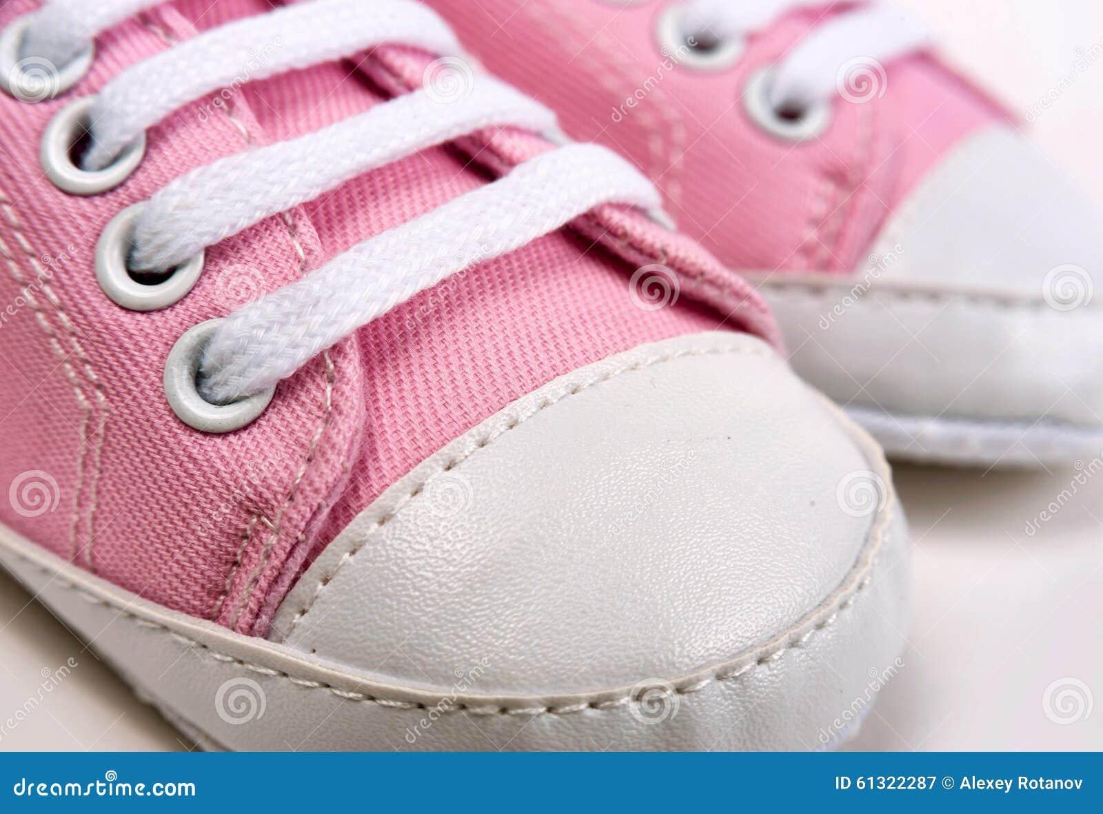 As sapatilhas cor-de-rosa bonitos do bebê fecham-se acima no cinza