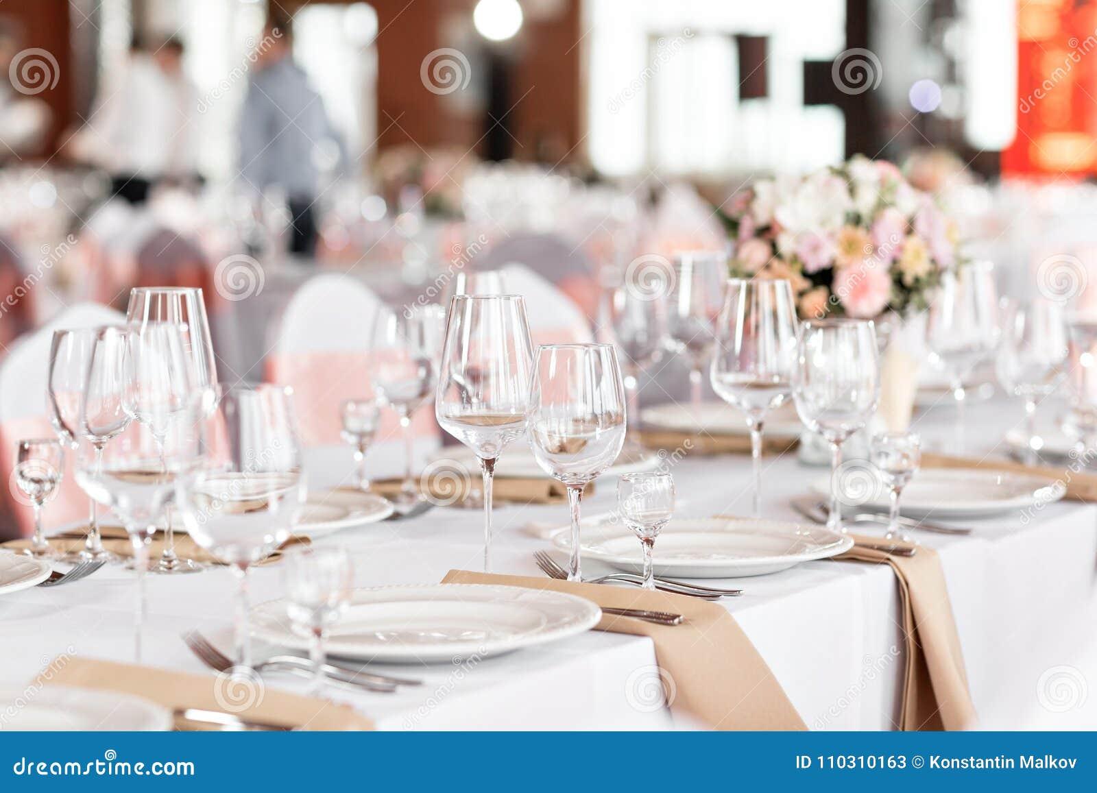 As tabelas ajustaram-se para um partido ou um copo de água do evento Jantar elegante luxuoso do ajuste da tabela em um restaurant